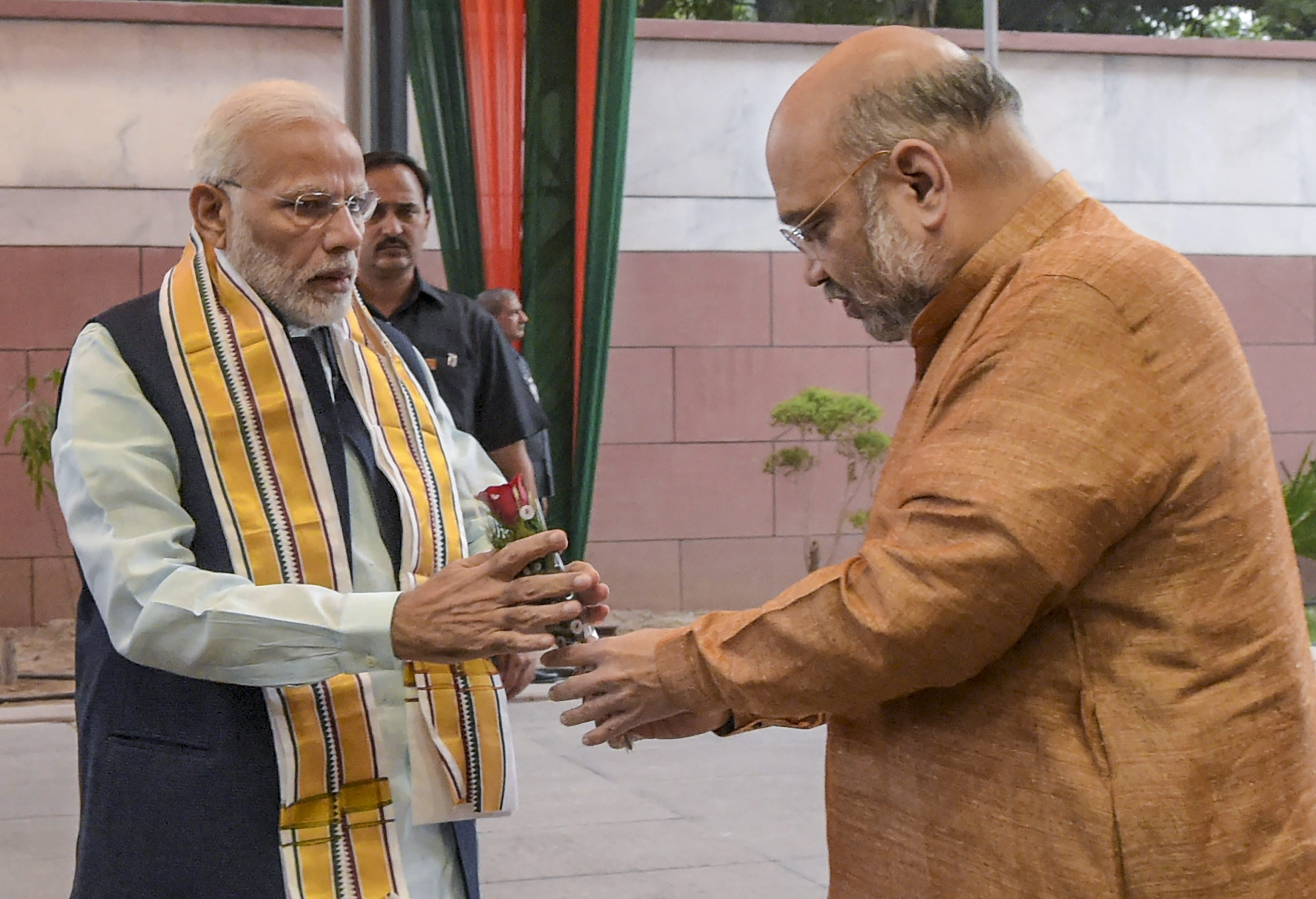Prime Minister Narendra Modi being welcomed by BJP President Amit Shah as he arrives for the party's Central Election Committee meeting in the view of the forthcoming Assembly polls in three states of Mizoram, Telangana and Madhya Pradesh, at party headquarters in New Delhi - PTI