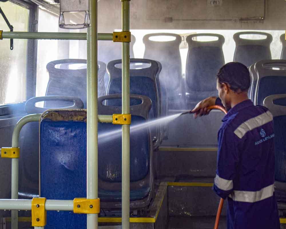 A worker carries out disinfection process of a bus in wake of the deadly novel coronavirus, at Peera Garhi bus depot in New Delhi - PTI