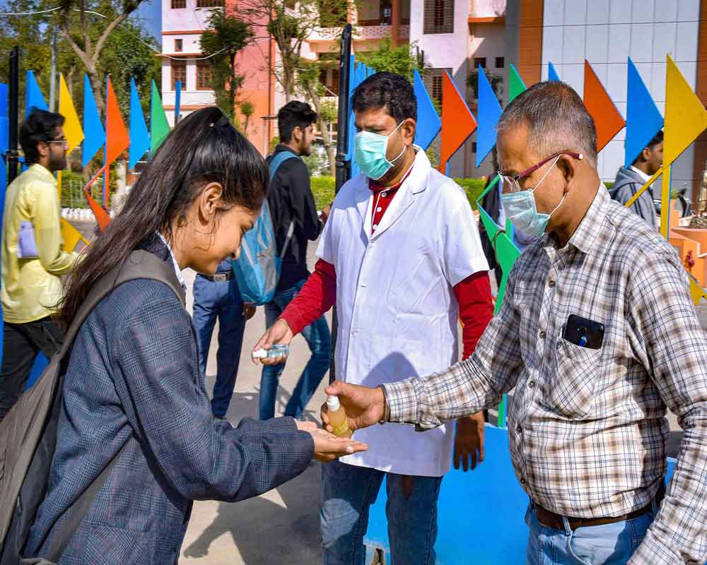 Students sanitize their hands amid coronavirus fears, outside a school ahead for their Central Board of Secondary Education (CBSE) Class 12 exams, in Bikaner - PTI