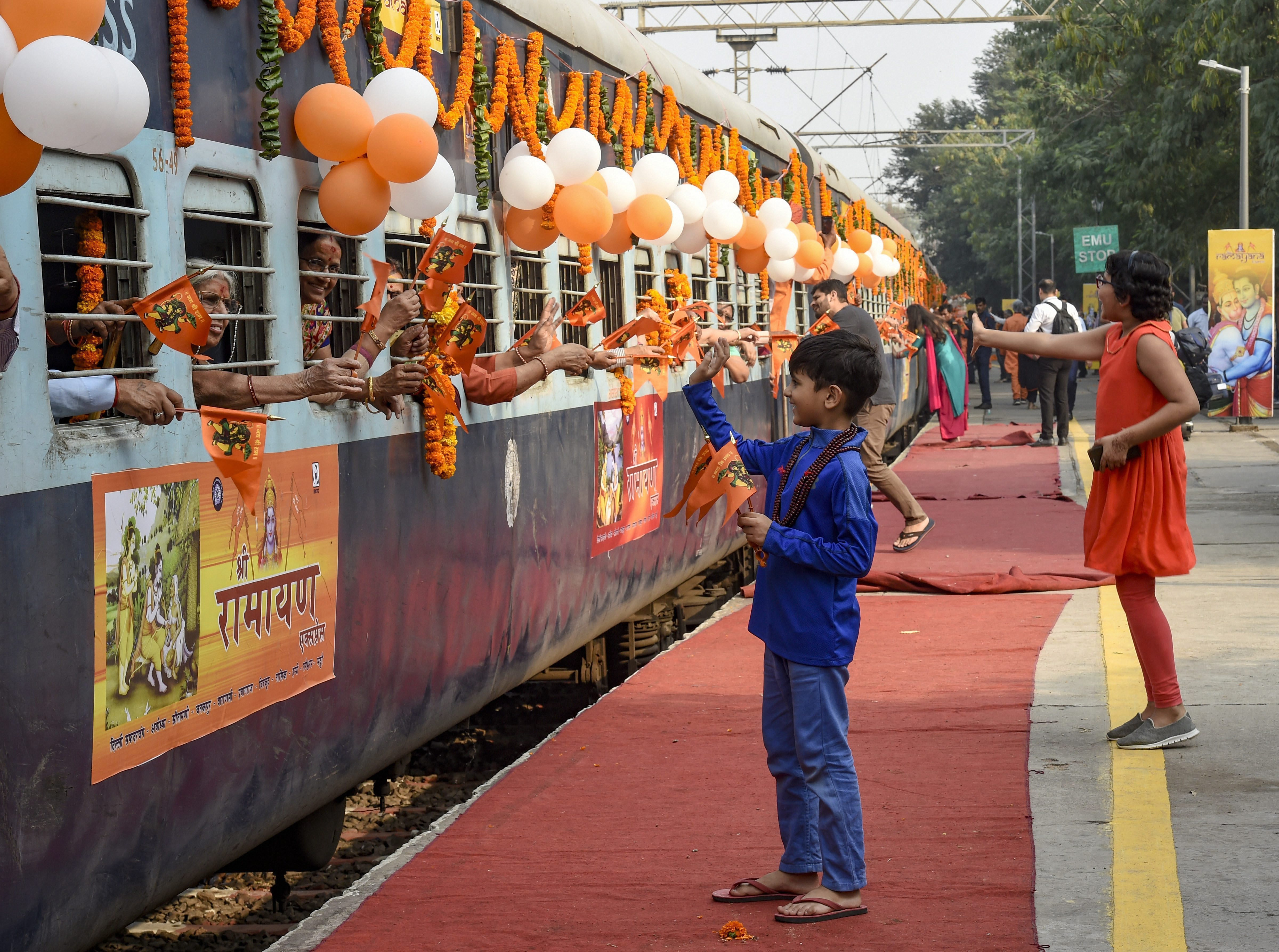 A boy waves at the passenger of Shri Ramayana Express train after it was flagged off at Safdarjung Railway Station in New Delhi - PTI