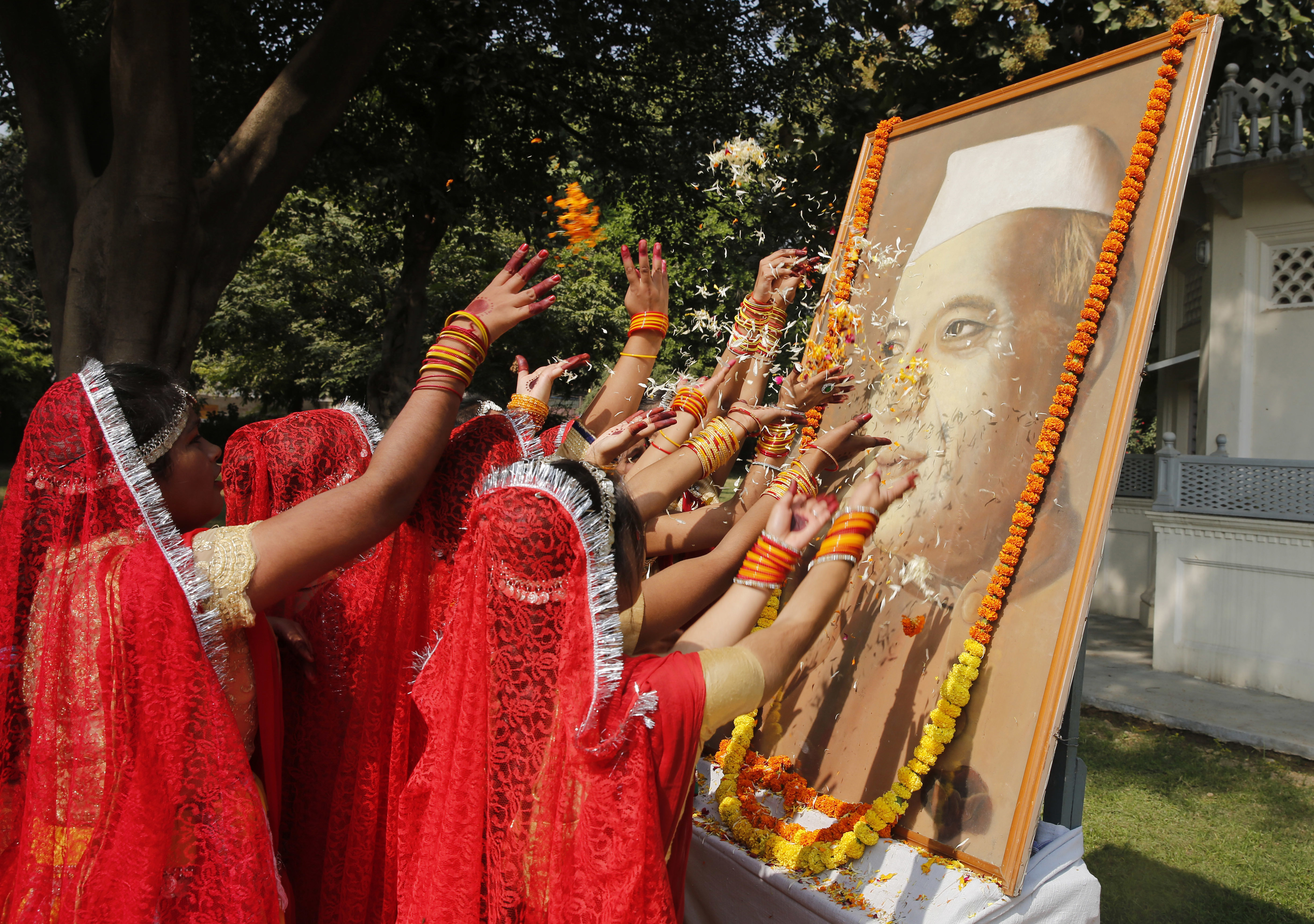 Indian children shower flower petals on a portrait of Jawaharlal Nehru, the country's first prime minister, on his birth anniversary at his ancestral home, Anand Bhawan, in Allahabad - AP