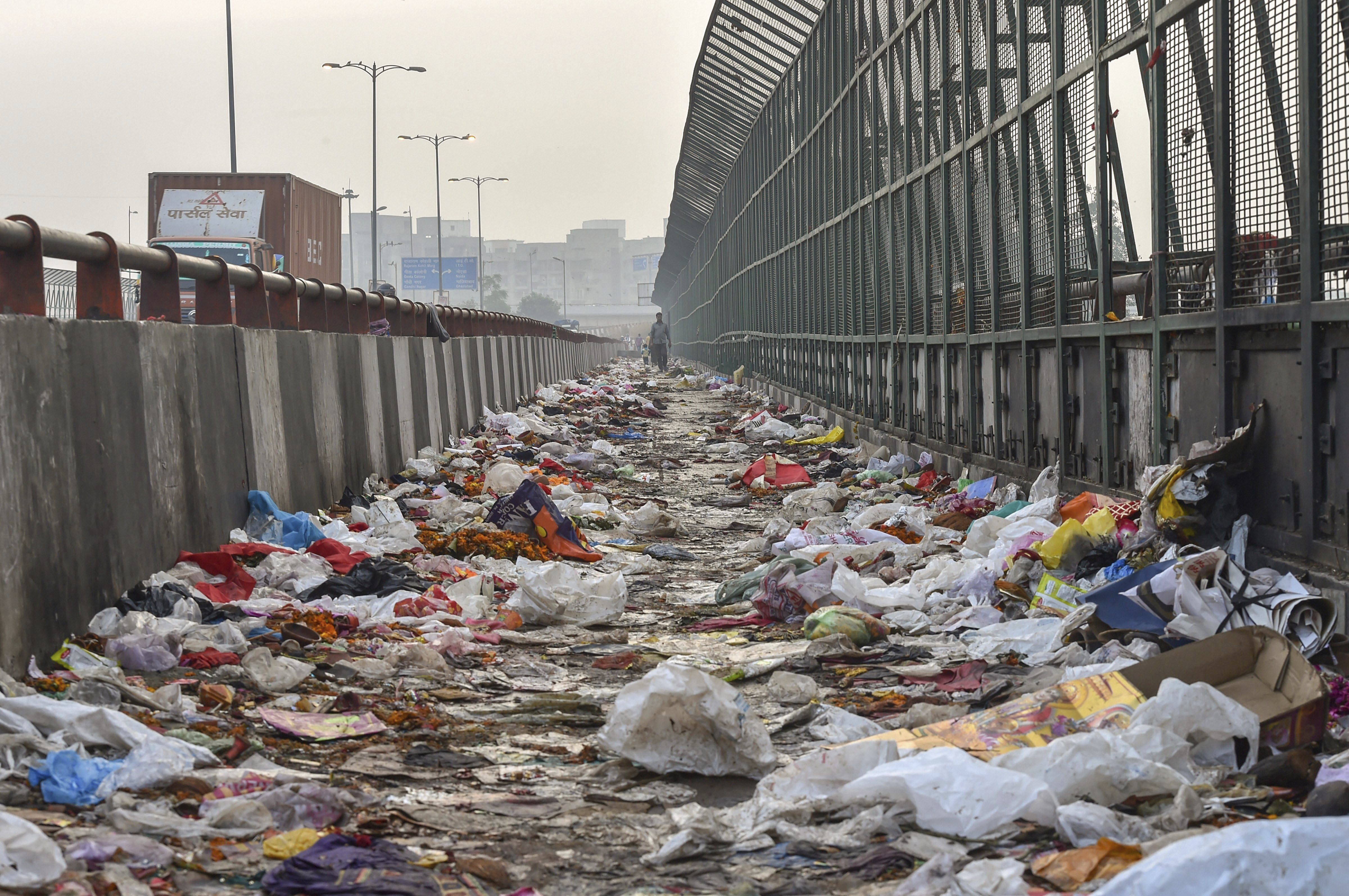 Plastic bags scattered on the pavement along Geeta Colony Setu over the River Yamuna, in New Delhi - PTI