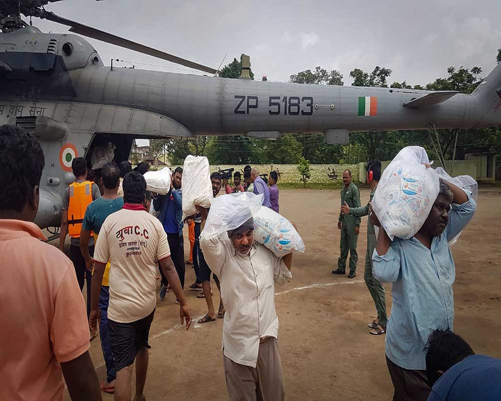 Jawans and villagers unload relief material, food and other items from an Indian Air Force helicopter for the flood victims at Shirol taluka in Kolhapur, Maharashtra - PTI