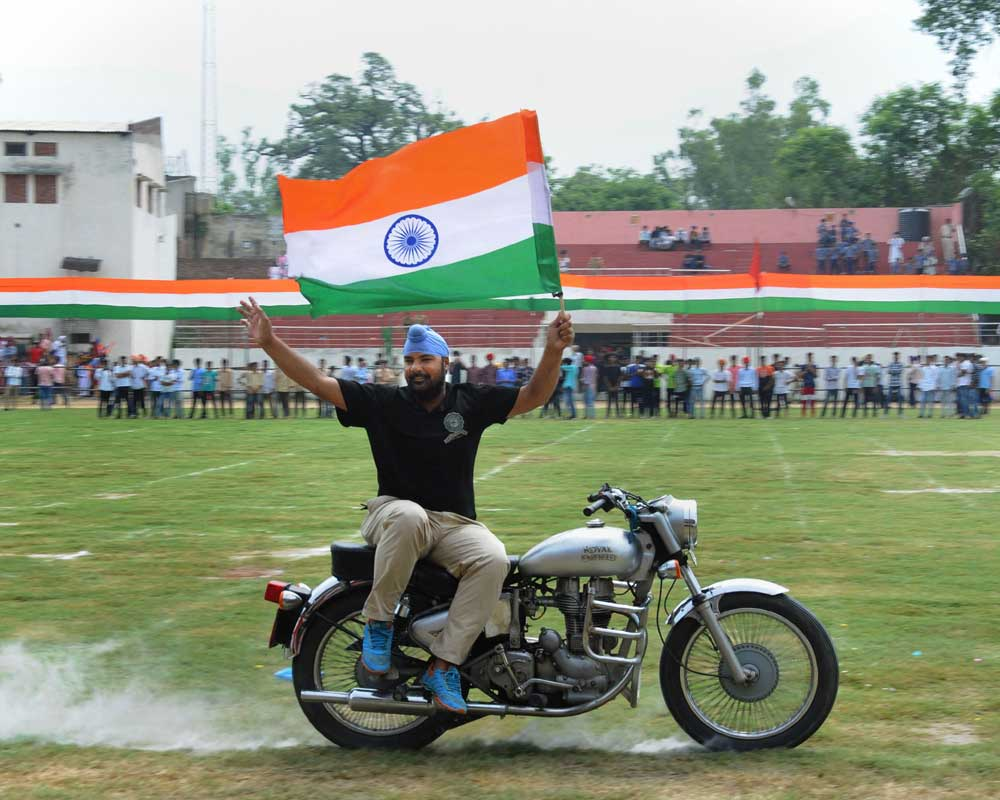 A stuntman performs on a bike during the full dress rehearsals for the 73rd Independence Day parade, in Amritsar - PTI