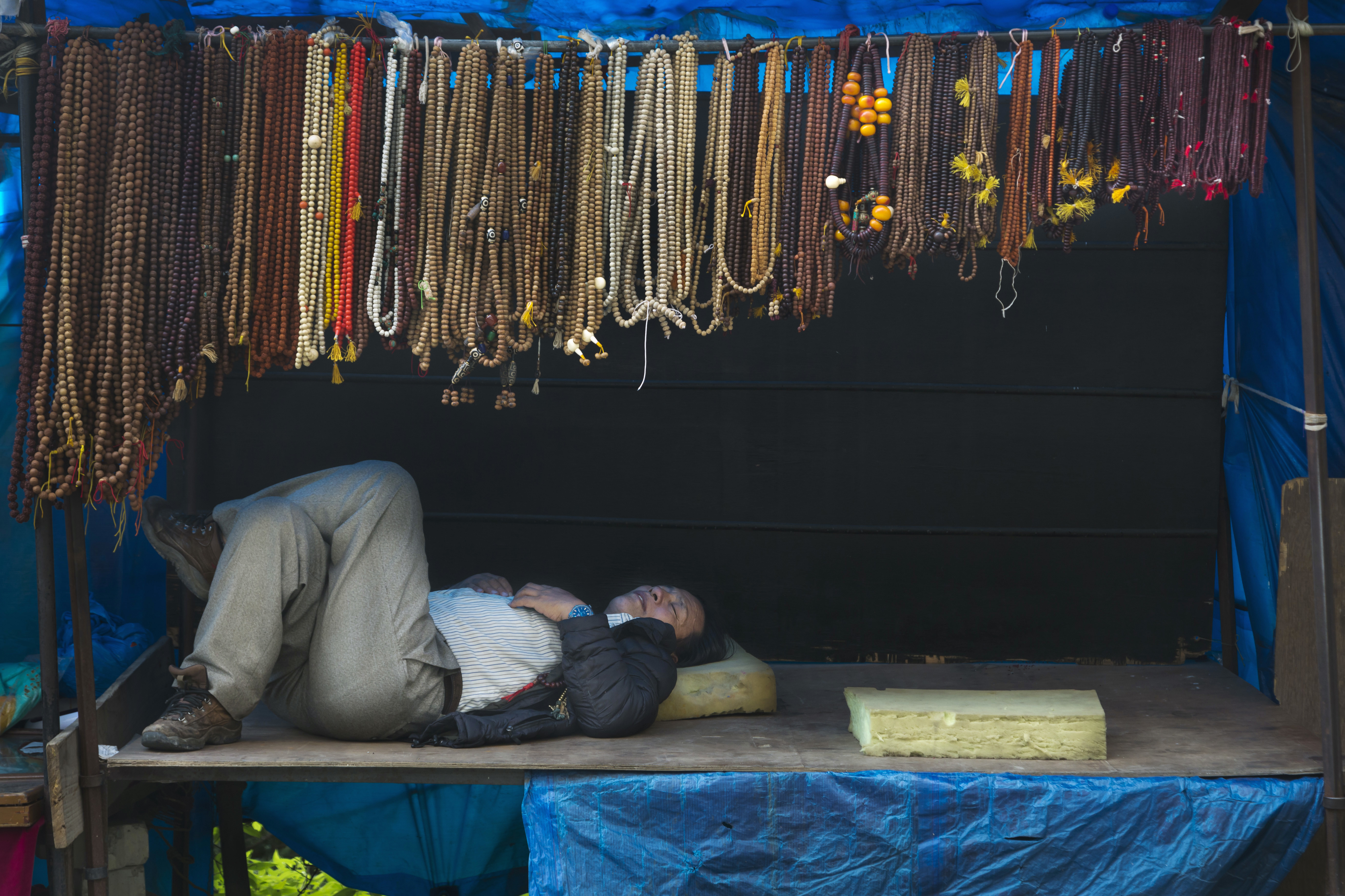 An exile Tibetan takes a nap in a roadside stall selling rosaries in Dharmsala, India - AP
