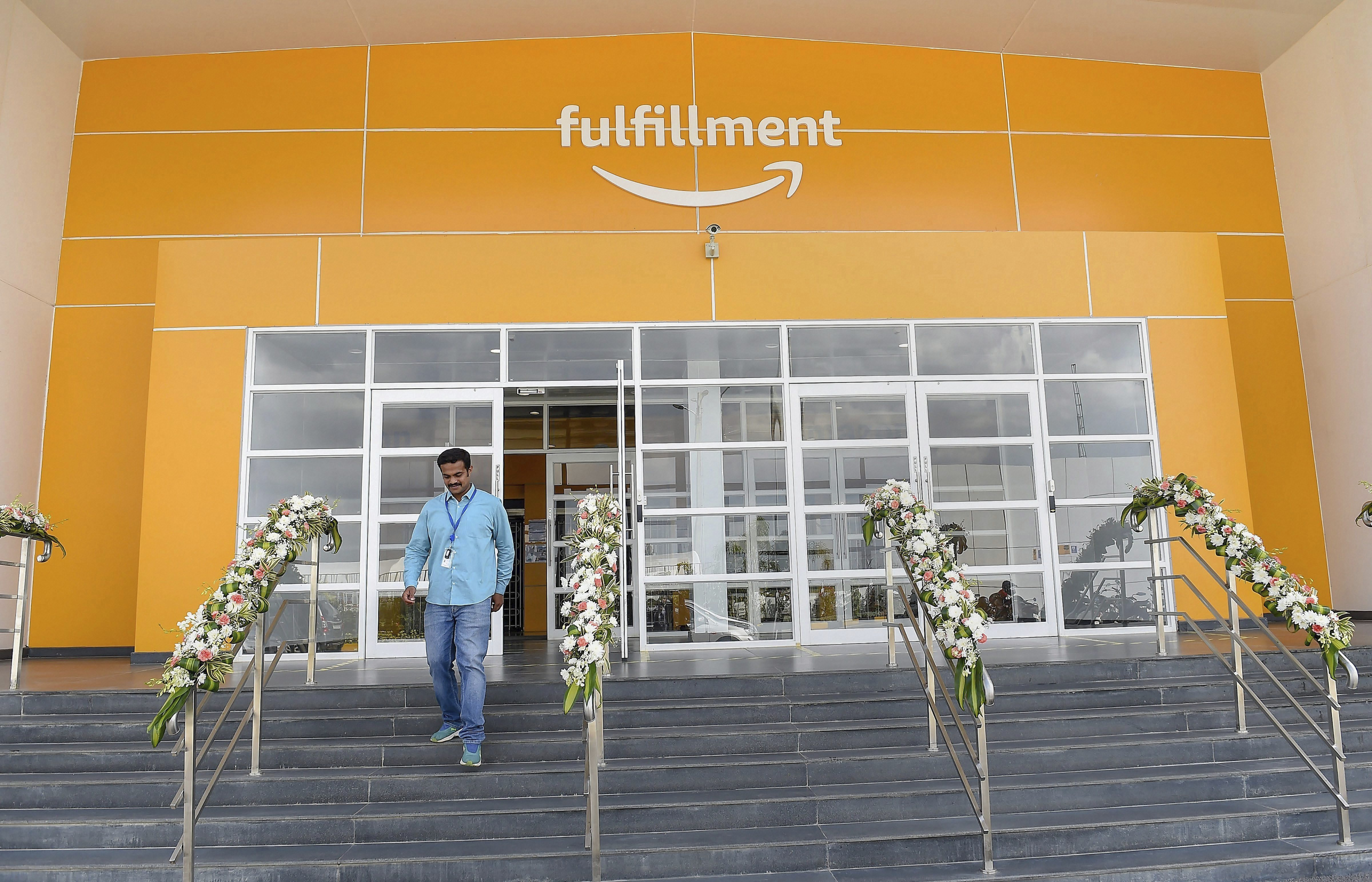 An employee comes out of Amazon's largest Fulfilment Centre in Karnataka - PTI