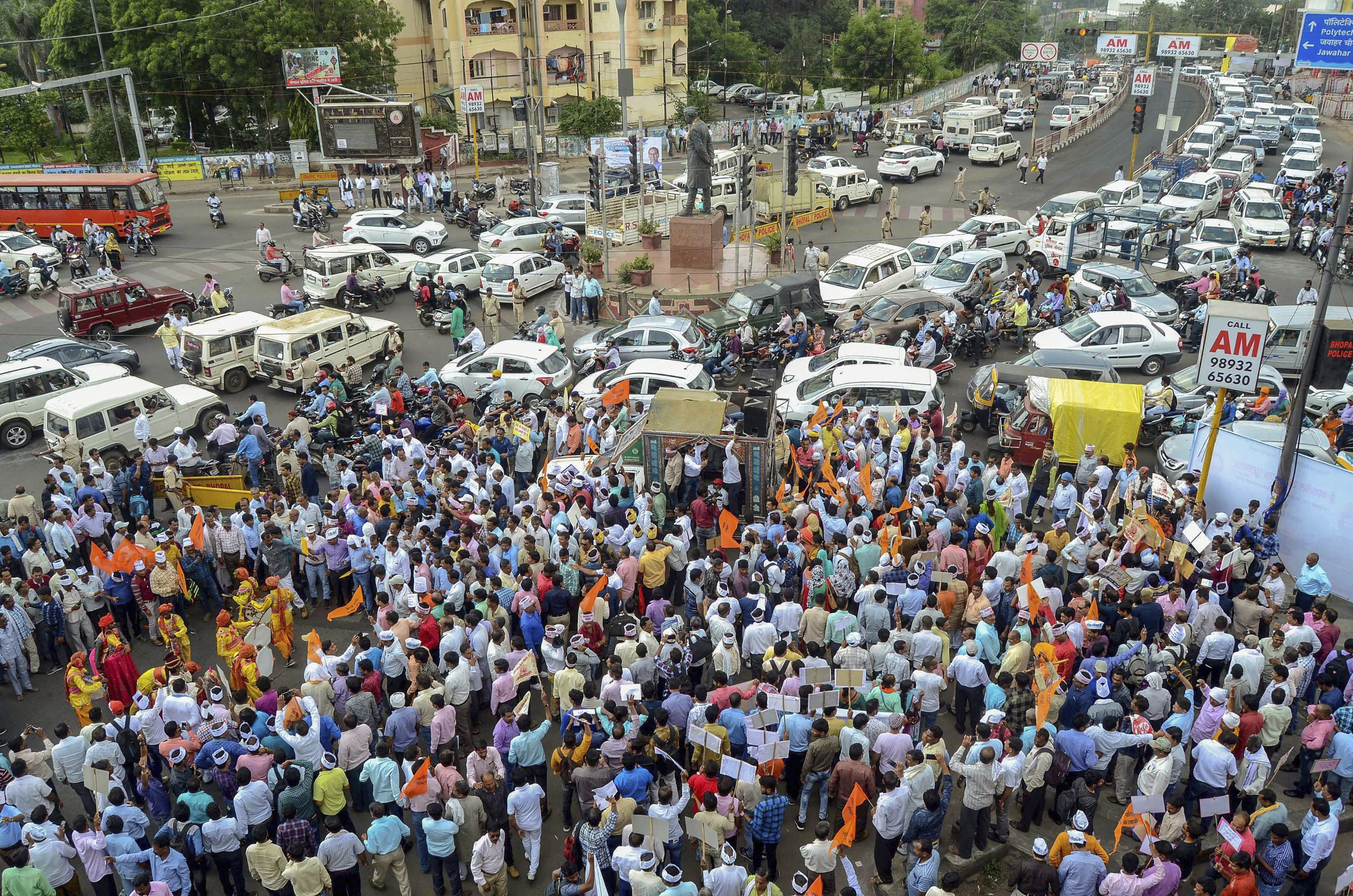 Madhya Pradesh Panchayat department employees stage a road blockade demanding seventh payscale and regularisation of their jobs, in Bhopal - PTI