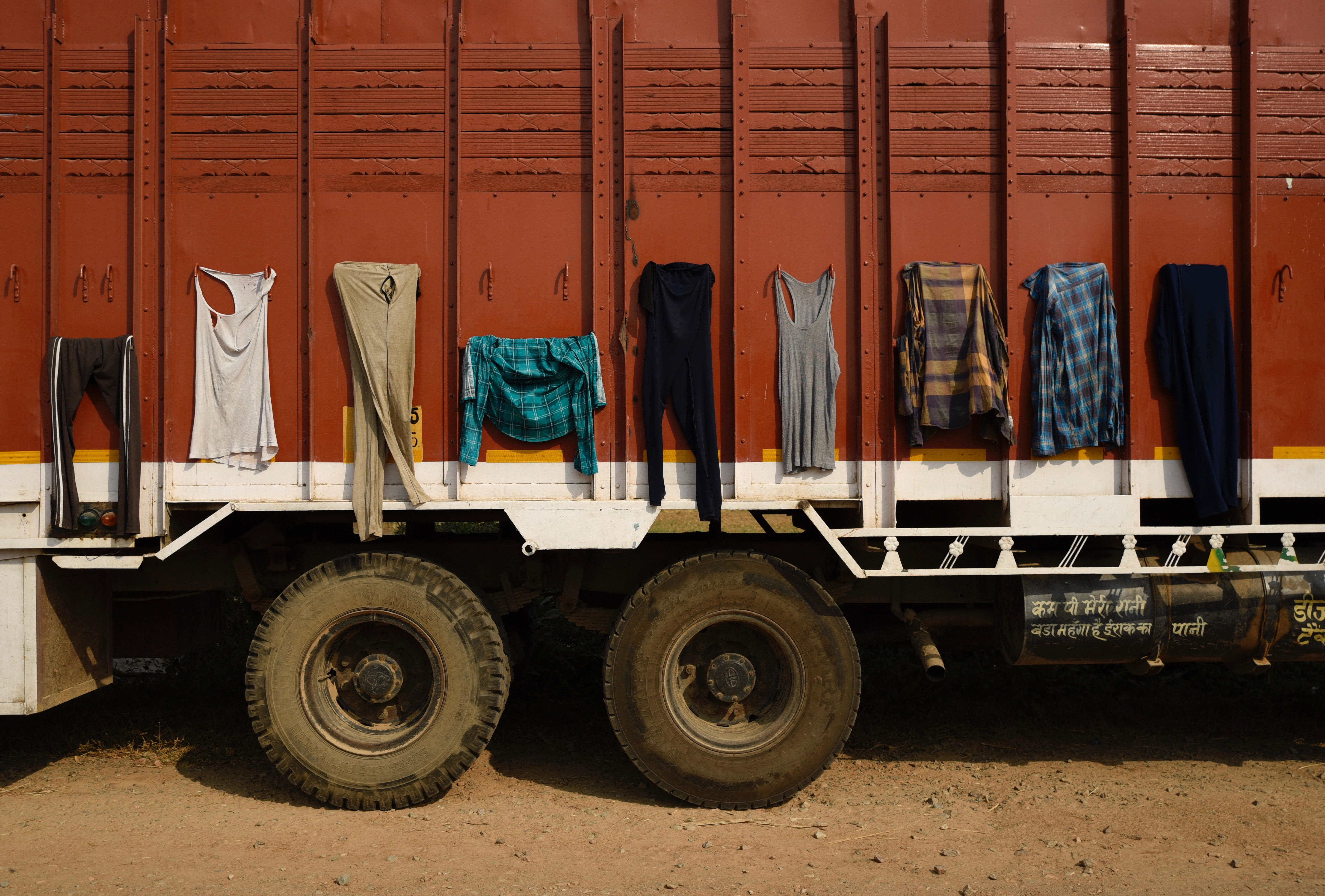 Clothes belonging to truck drivers are hung out to dry on the body of a truck in Mathura, India - AP