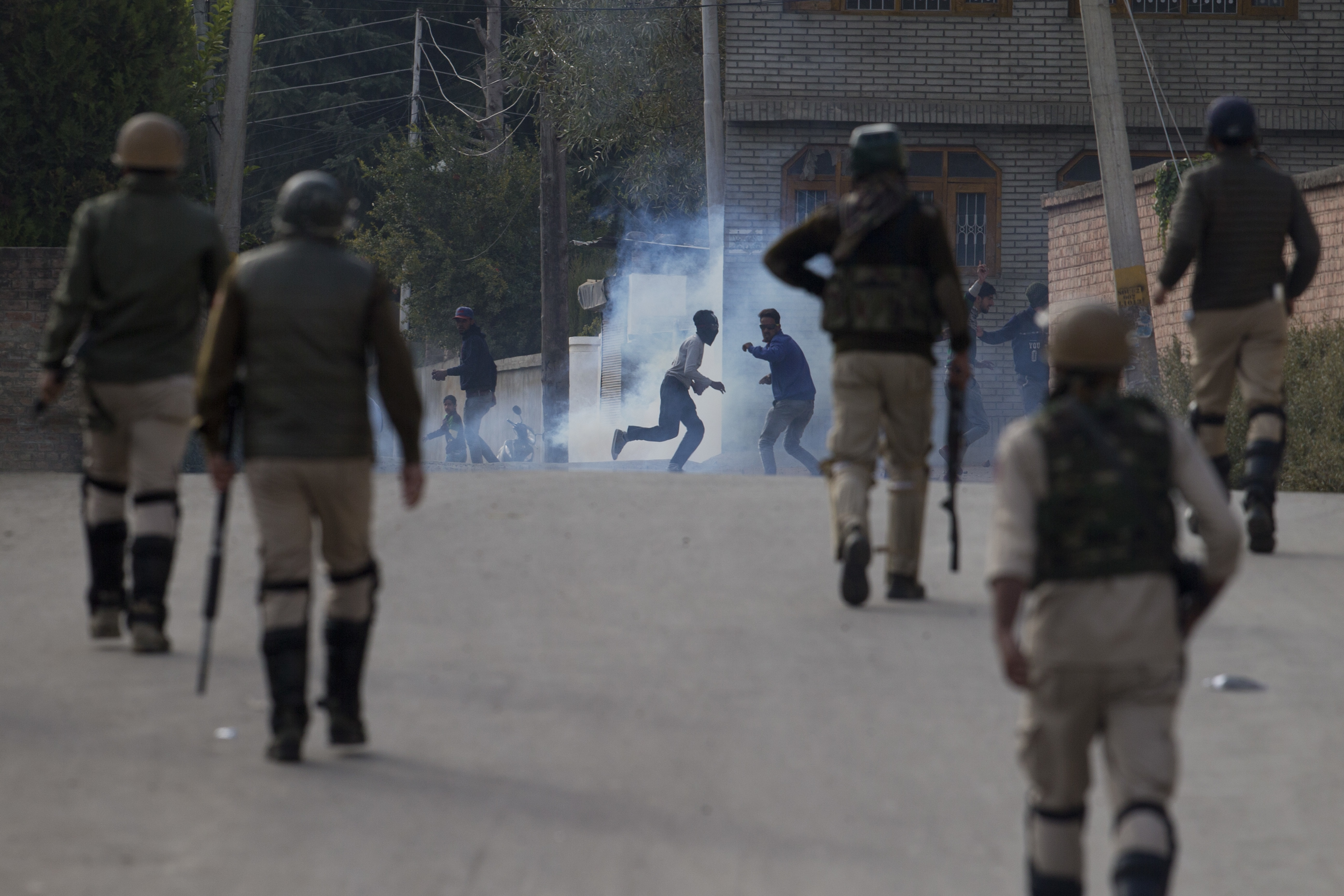 Kashmiri protesters run for cover amid tear gas shell fired at them by Indian security forces in Srinagar, India - AP
