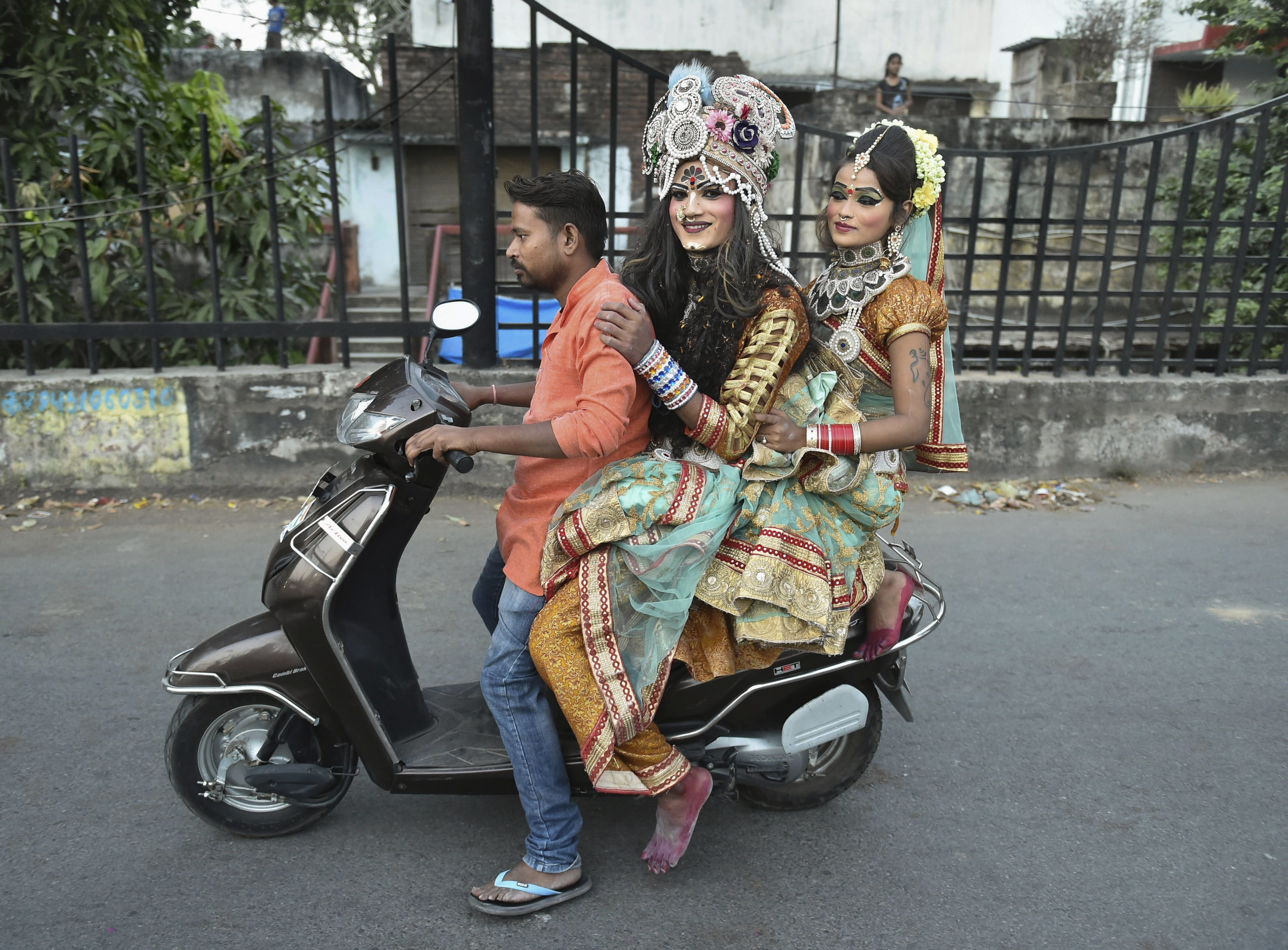 Artists, in colourful attire, leave after immersion of idol of Goddess Durga in Lucknow - PTI