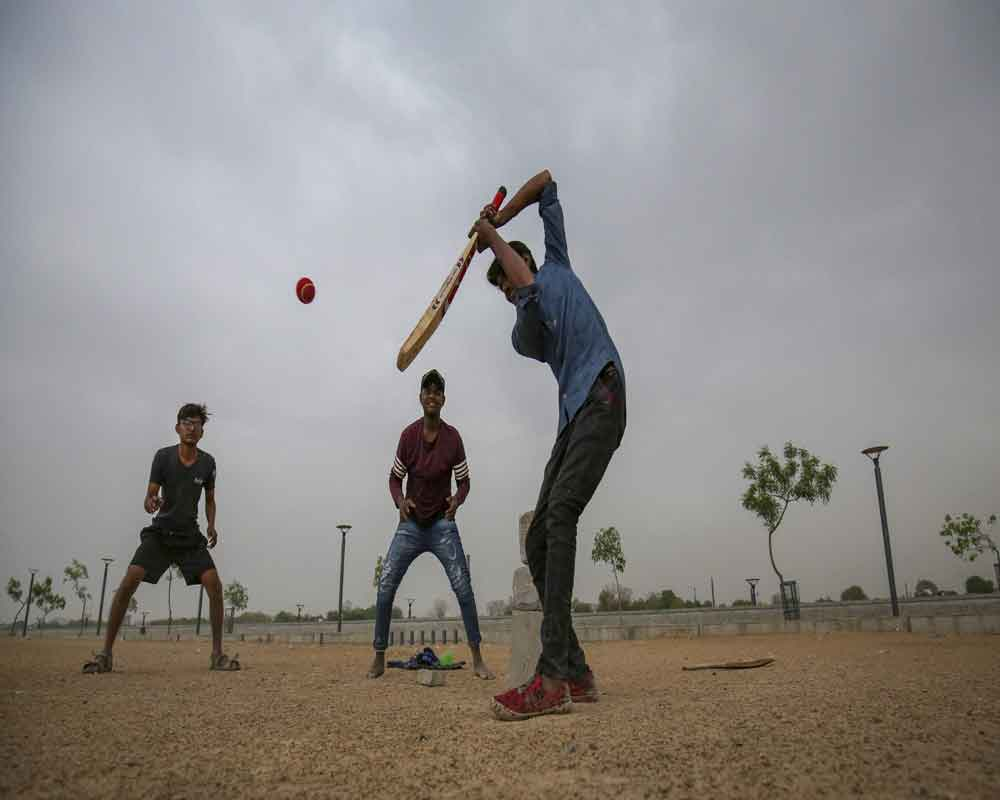Boys play cricket during a cloudy day, in Ahmedabad - PTI