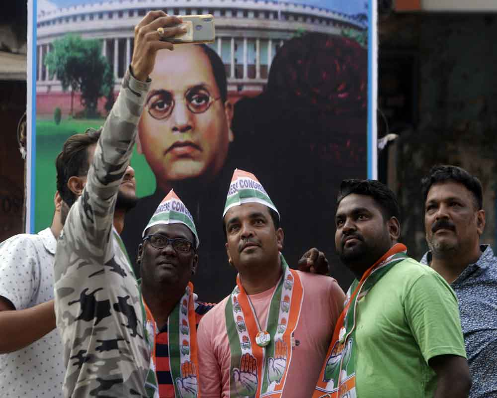 Congress party workers take selfie in front of a poster of Bhimrao Ambedkar during an election campaign in Mumbai – AP