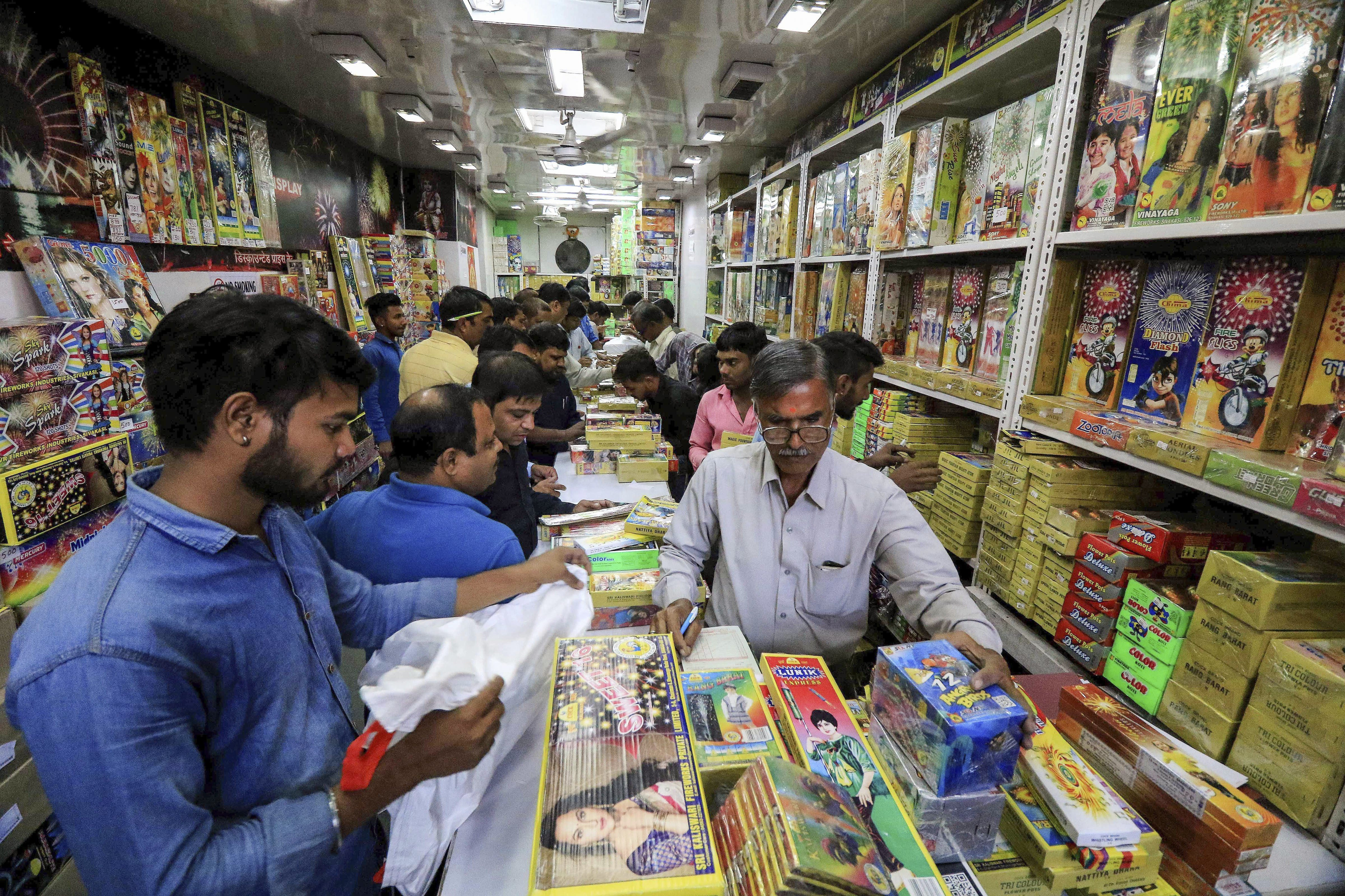 People buy crakers at a shop on the occasion of 'Dhanteras' festival, in Jaipur - PTI