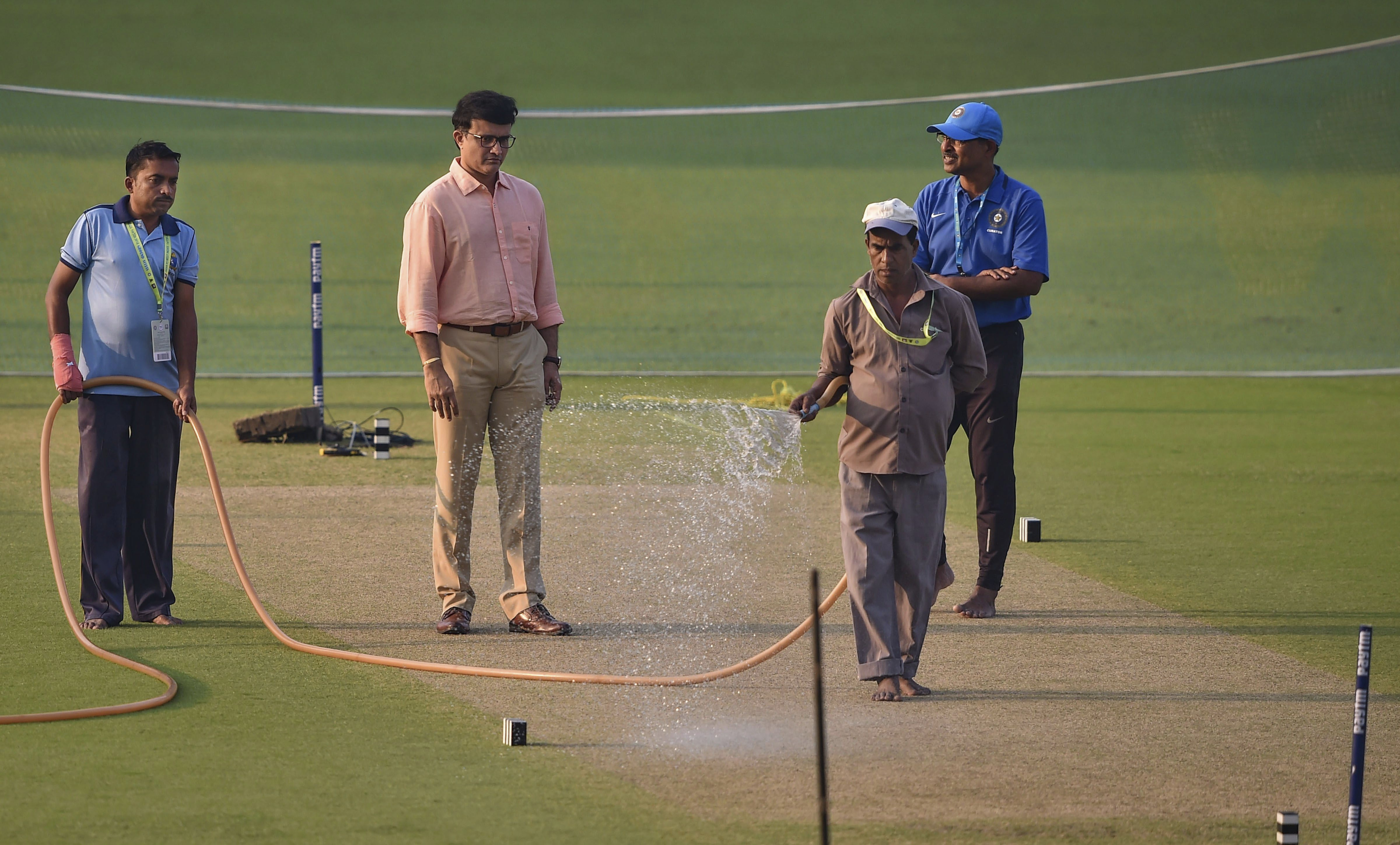 A groundsman sprays water on the pitch as CAB President Sourav Ganguly inspects on the eve of 1st T20 match between India and West Indies at Eden Garden, in Kolkata - PTI