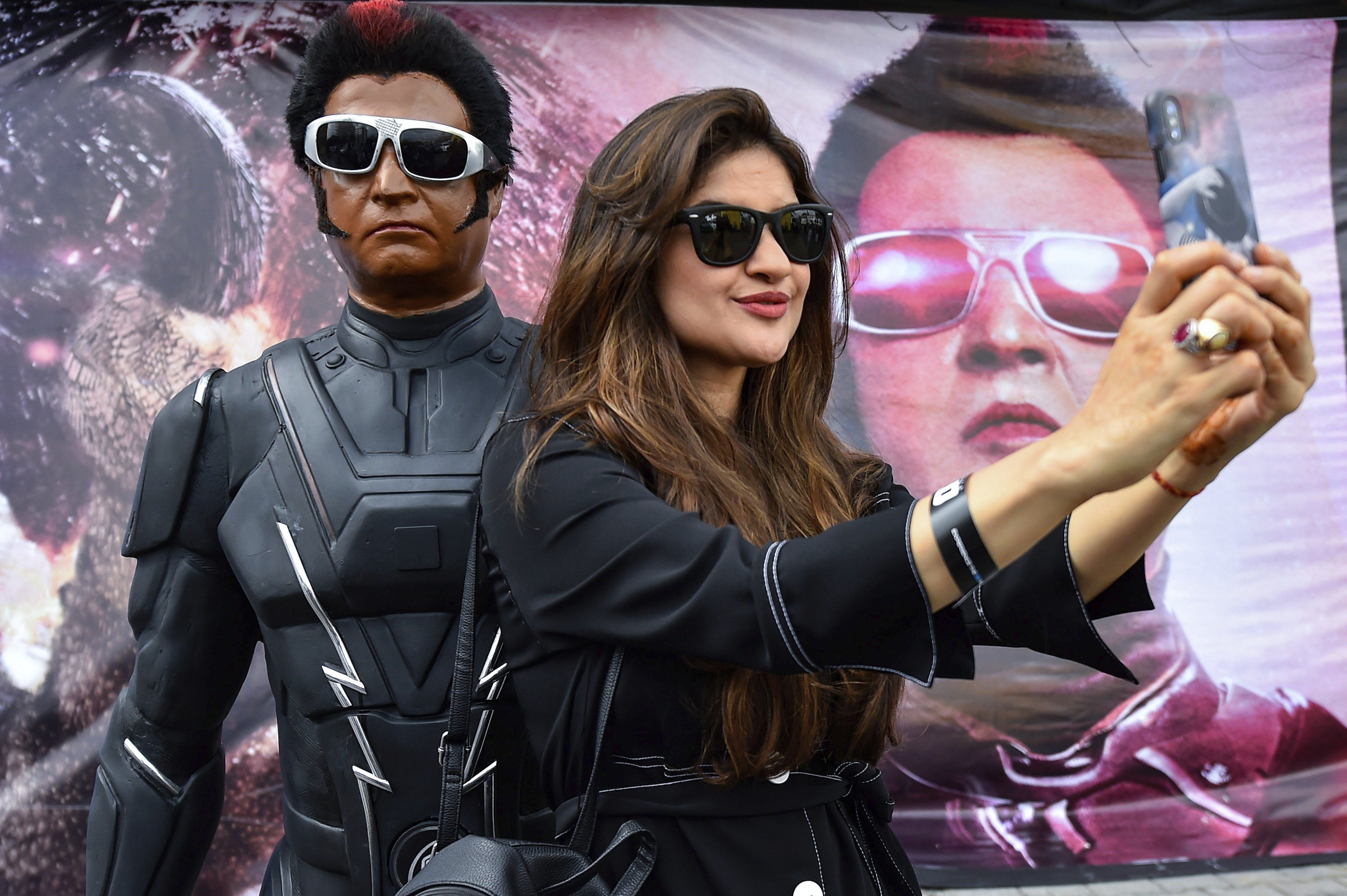A fan takes a selfie with a statue of Tamil Superstar Rajinikanth at the launch of the trailer of film '2.0' in Chennai - PTI