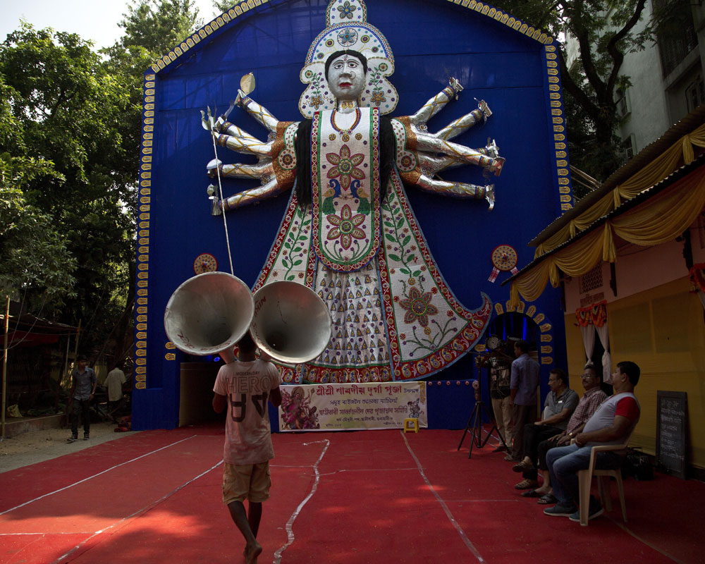 An Indian laborer prepares to install loud speakers at a worship venue of Hindu goddess Durga on the eve of Durga Puja festival in Gauhati - AP