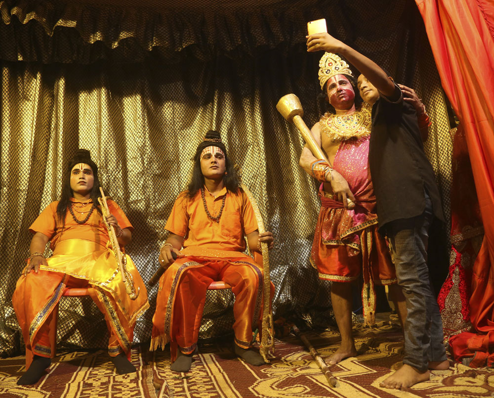 A boy takes a selfie with Indian artists dressed up for 'Ramleela', a theatre performance depicting the Hindu epic Ramayana, as part of Dussehra festival celebrations in Mumbai - AP