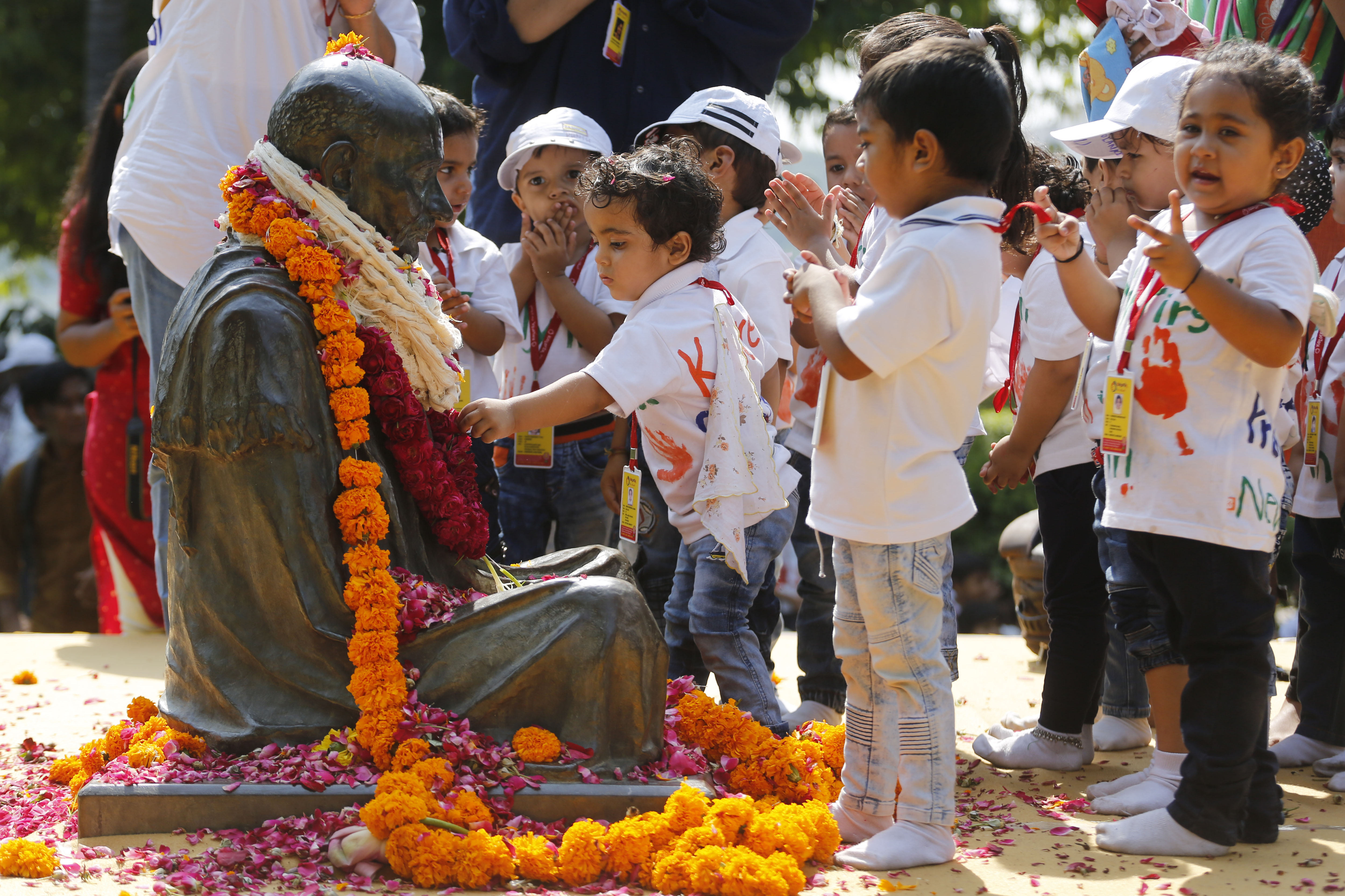 Children pay tributes to a statue of Mahatma Gandhi, during an all religion prayer at the Gandhi Ashram to mark his birth anniversary in Ahmadabad - AP