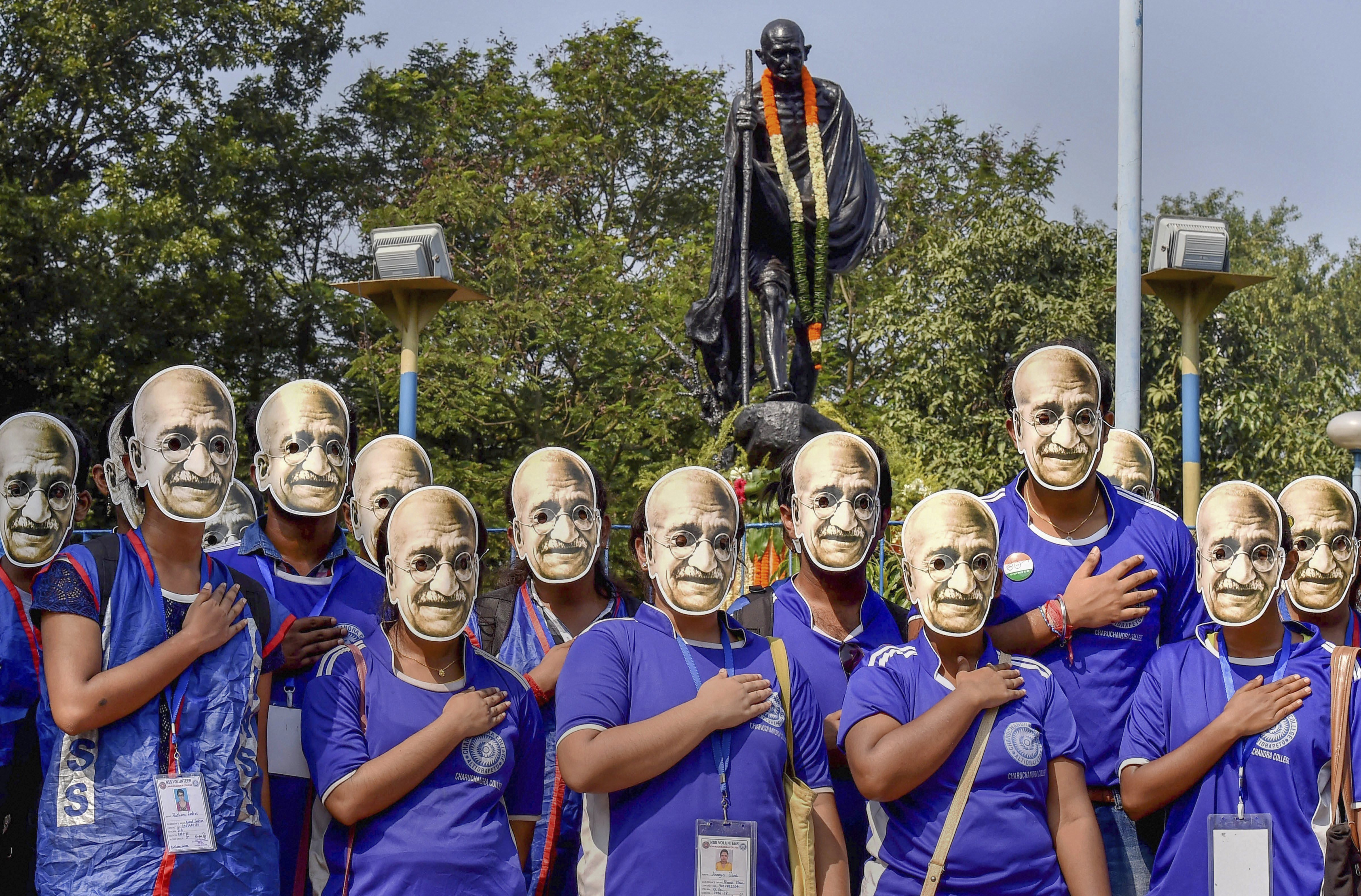 Youth wearing masks of Mahatma Gandhi pose for a photograph in front of a Gandhi statue during his 149th birth anniversary celebrations, in Kolkata - PTI