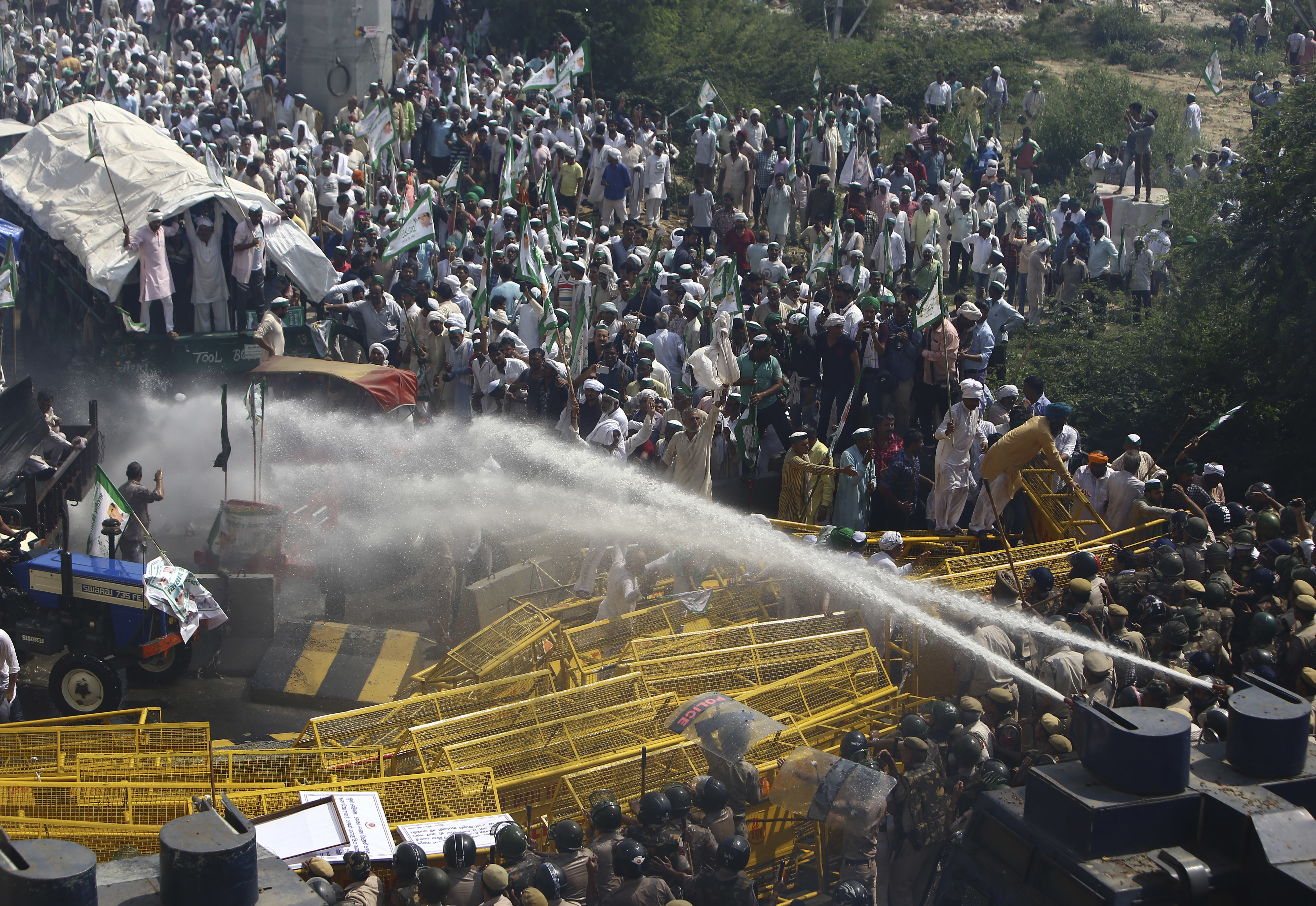 Indian police use water cannons to disperse farmers who were marching to the Indian capital after stopping them at New Delhi's border with neighboring Uttar Pradesh state - AP