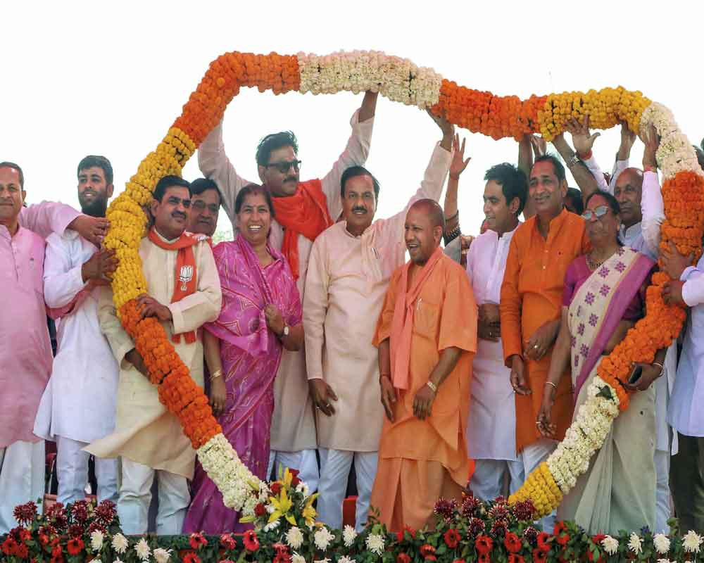 Uttar Pradesh Chief Minister Yogi Adityanath being garlanded at an election rally in support of Union Minister and BJP candidate Mahesh Sharma, ahead of the Lok Sabha elections - PTI
