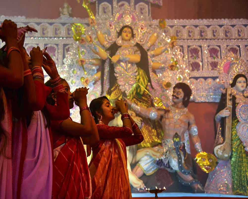 Devotees blow conchshells in front of an idol of goddess Durga on 'Maha Shashti', the sixth day of the ongoing Durga Puja festival, in Guwahati - PTI