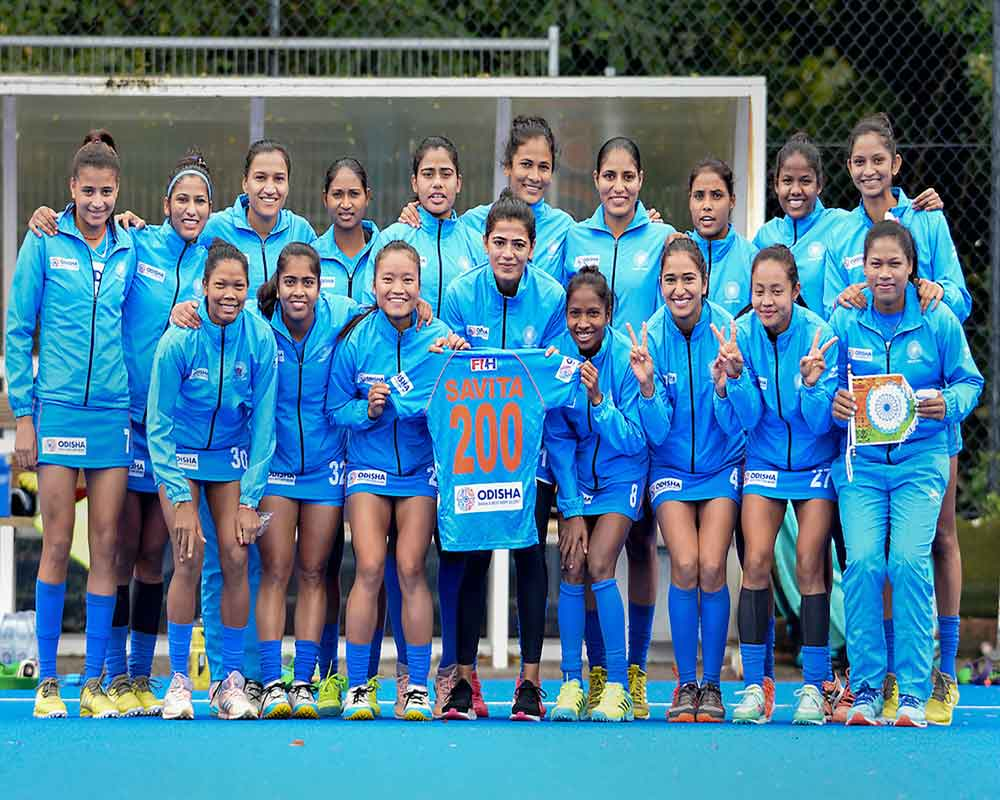 Indian hockey team goalkeeper Savita Punia (C) holds up a jersey '200' to celebrate her milestone of achieving 200 international caps ahead of their fifth and last match of their Tour of England, in Marlow - PTI