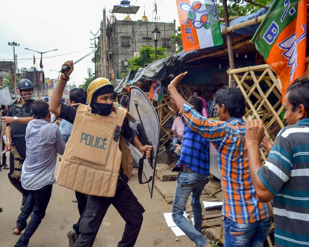 A policeman baton-charges at a BJP activist during their rally to submit deputation on the cut-money issue before Asansol Municipal Corporation, in Asansol - PTI