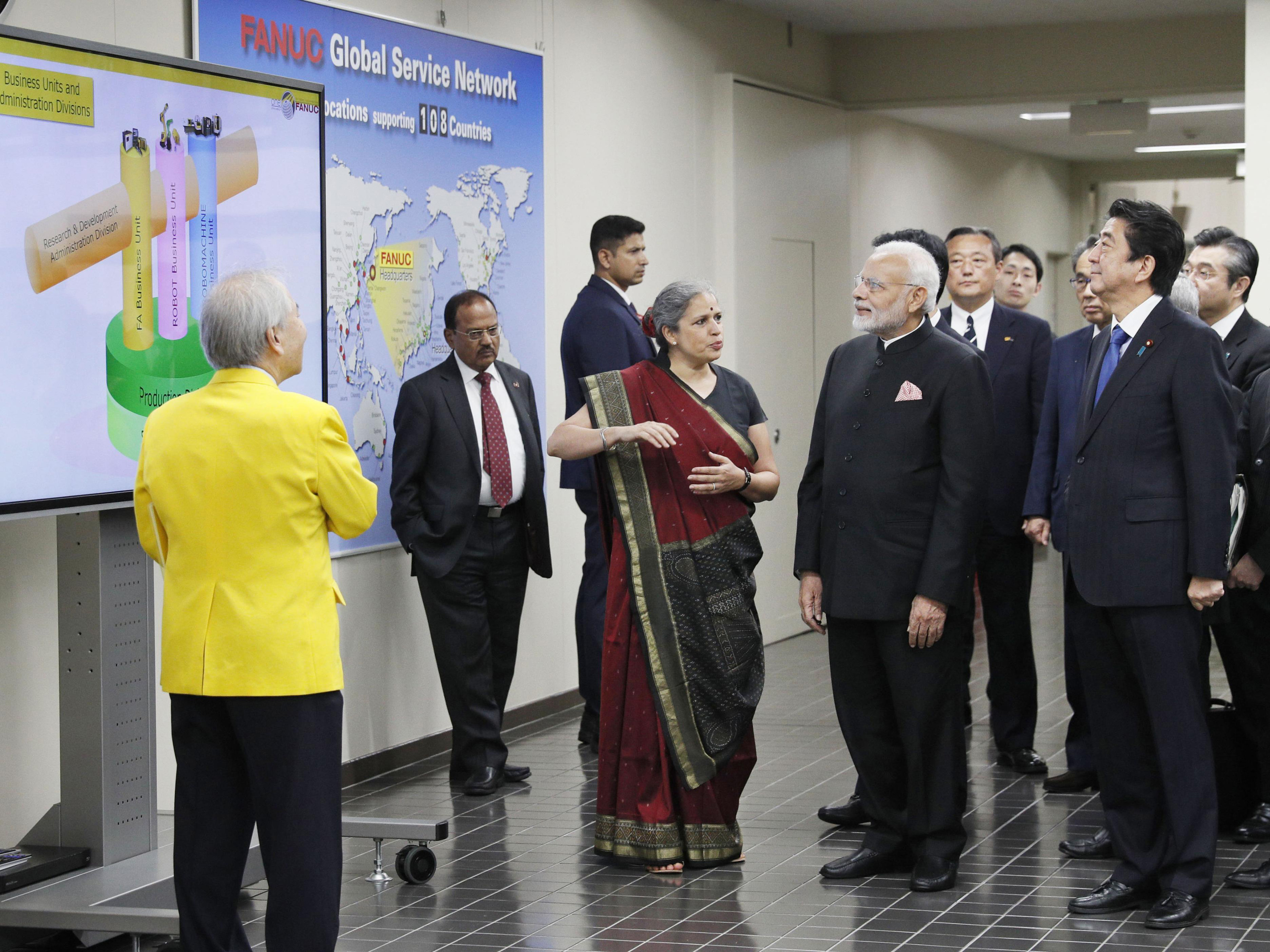 Indian Prime Minister Narendra Modi, second right in front, and Japanese Prime Minister Shinzo Abe, front right, visit a plant of major Japanese robot maker Fanuc in Ohinomura - AP