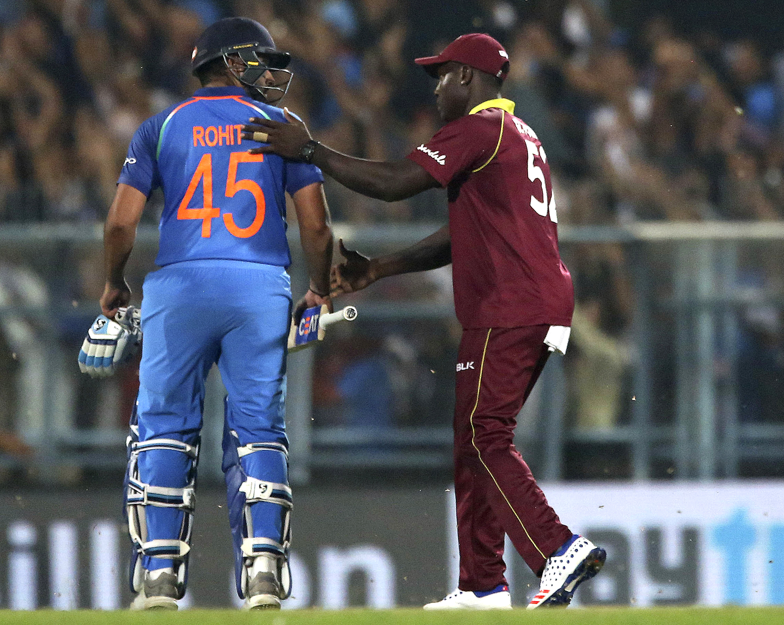 West Indies' Rovman Powell, right, greets India's Rohit Sharma after India won the first one-day international cricket match between India and West Indies in Gauhati - AP