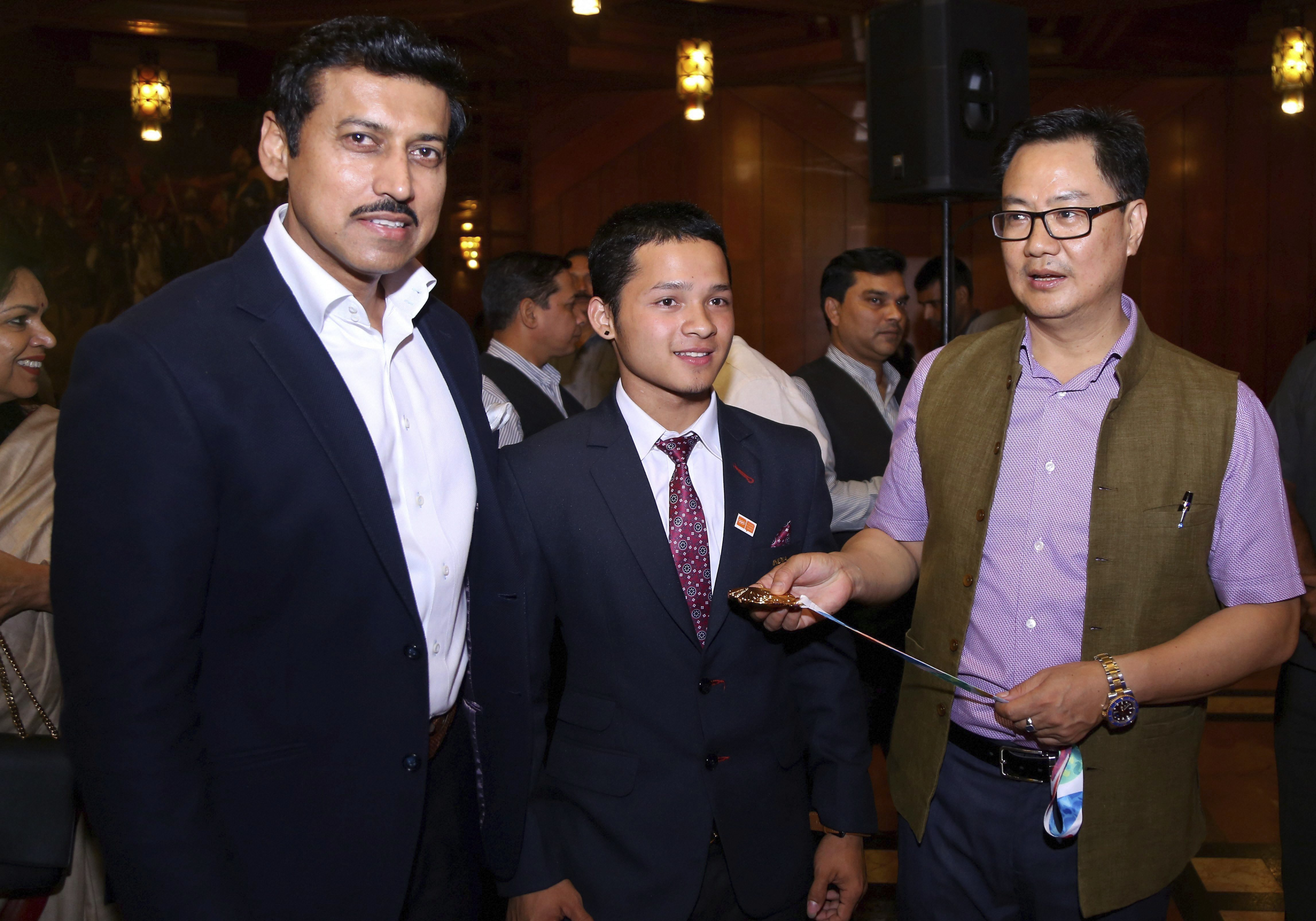 Minister of State for Youth Affairs & Sports, Rajyavardhan Singh Rathore and Minister of State for Home Affairs, Kiren Rijiju with Jeremy Lalrinnunga, gold medalist, weightlifting during the winners of the Summer Youth Olympics 2018 felicitation ceremony, in New Delhi - PTI