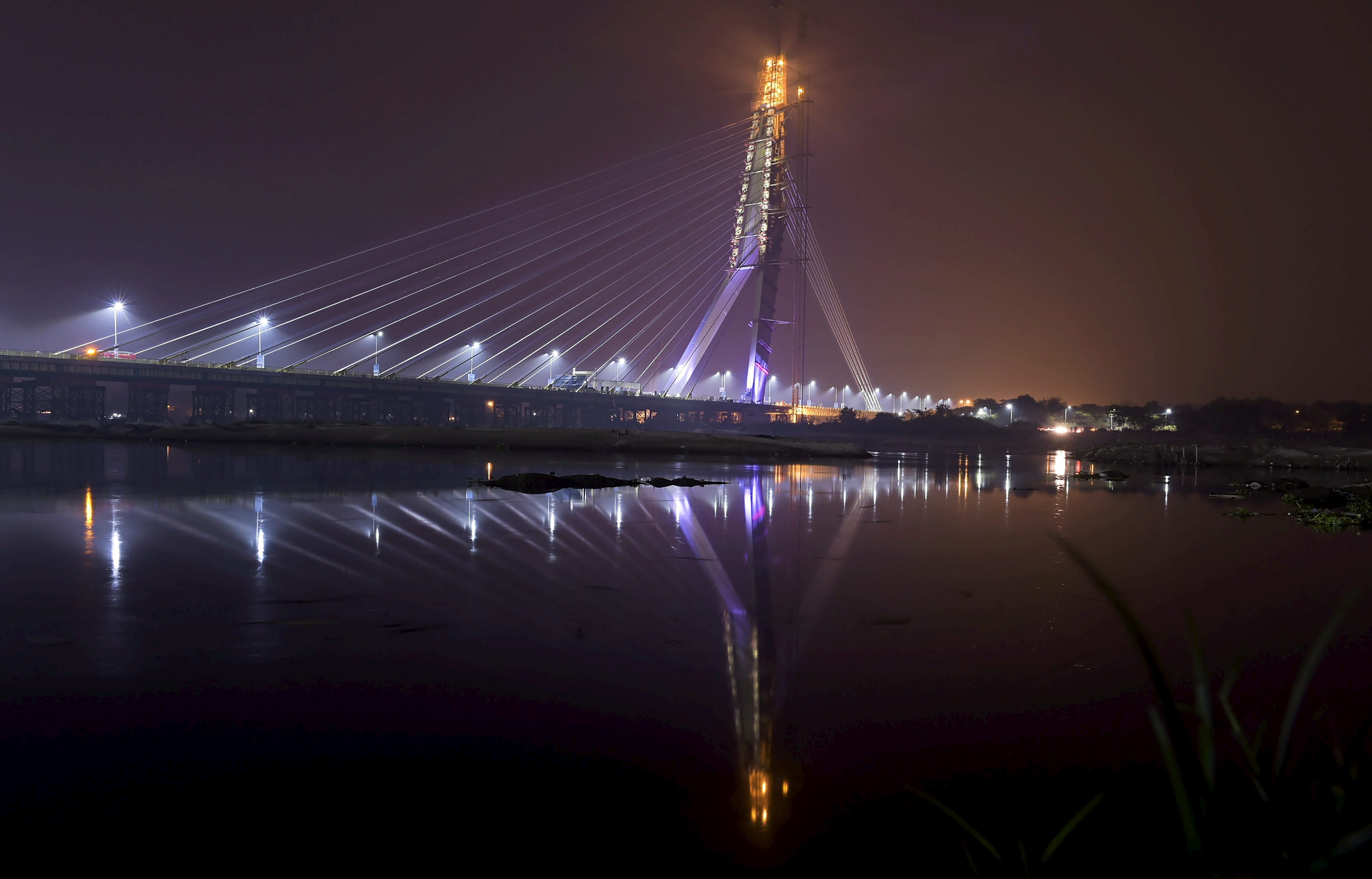 A view of the newly inaugurated Signature Bridge over Yamuna river during a laser show, at Wazirabad in New Delhi - PTI