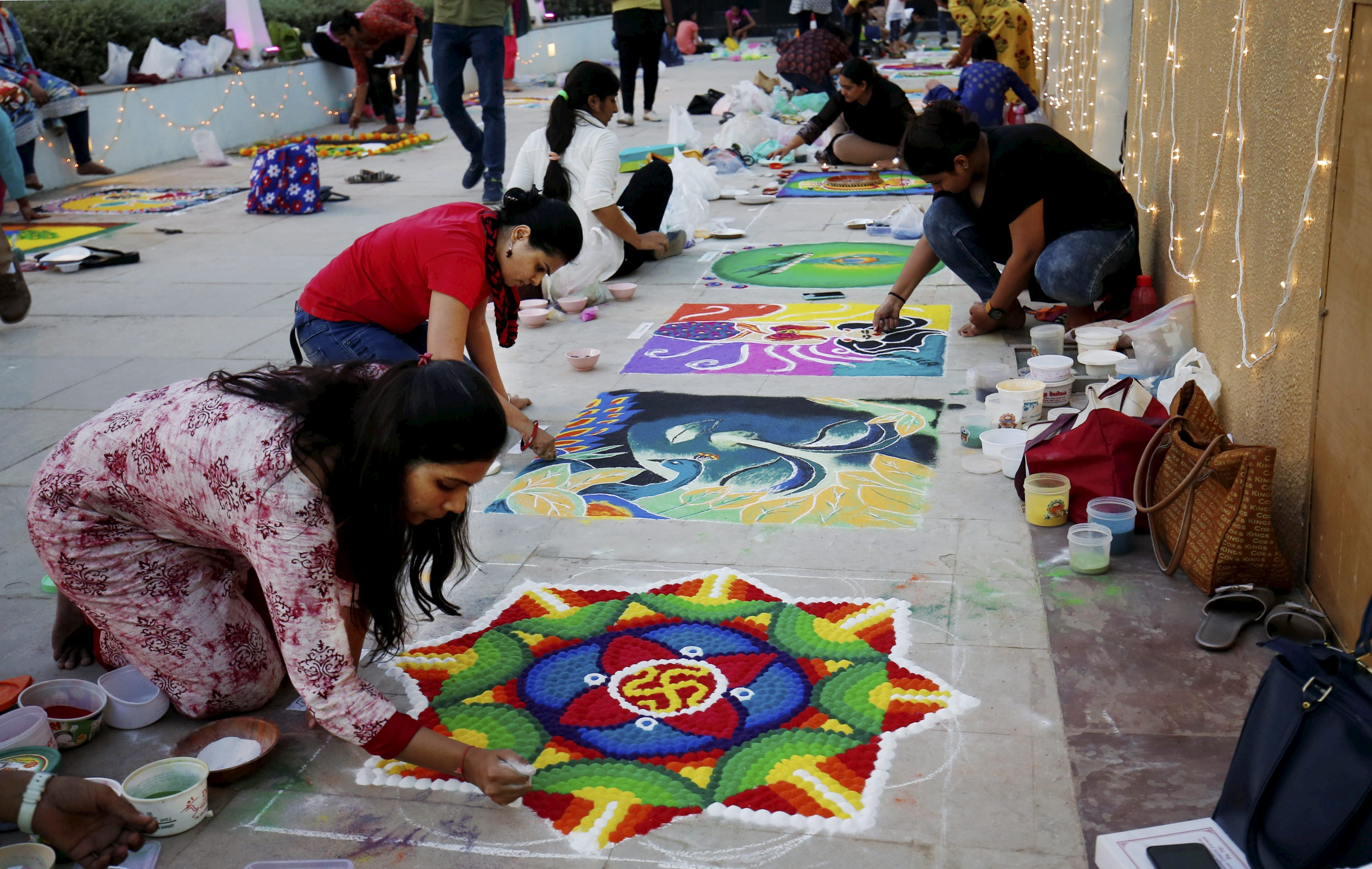 Women make 'rangoli' out of coloured powders during a competition ahead of the festival of Diwali in Ahmedabad - PTI