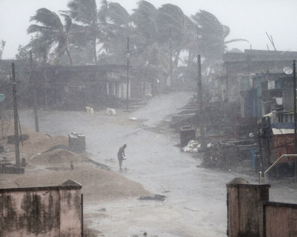 a man stands near Arjipalli beach during rain and strong winds caused by a cyclonic storm named Titli, or Butterfly, near Gopalpur on the Bay of Bengal coast, Ganjam district, in the eastern Indian state of Orissa - AP