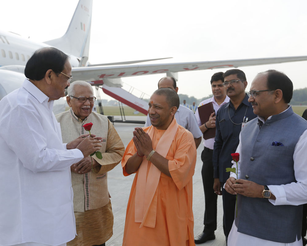 Indian Vice President Venkaiah Naidu is welcomed by Uttar Pradesh state Chief Minister Yogi Adityanath, center, as he arrives at Bamrauli airport in Allahabad - AP