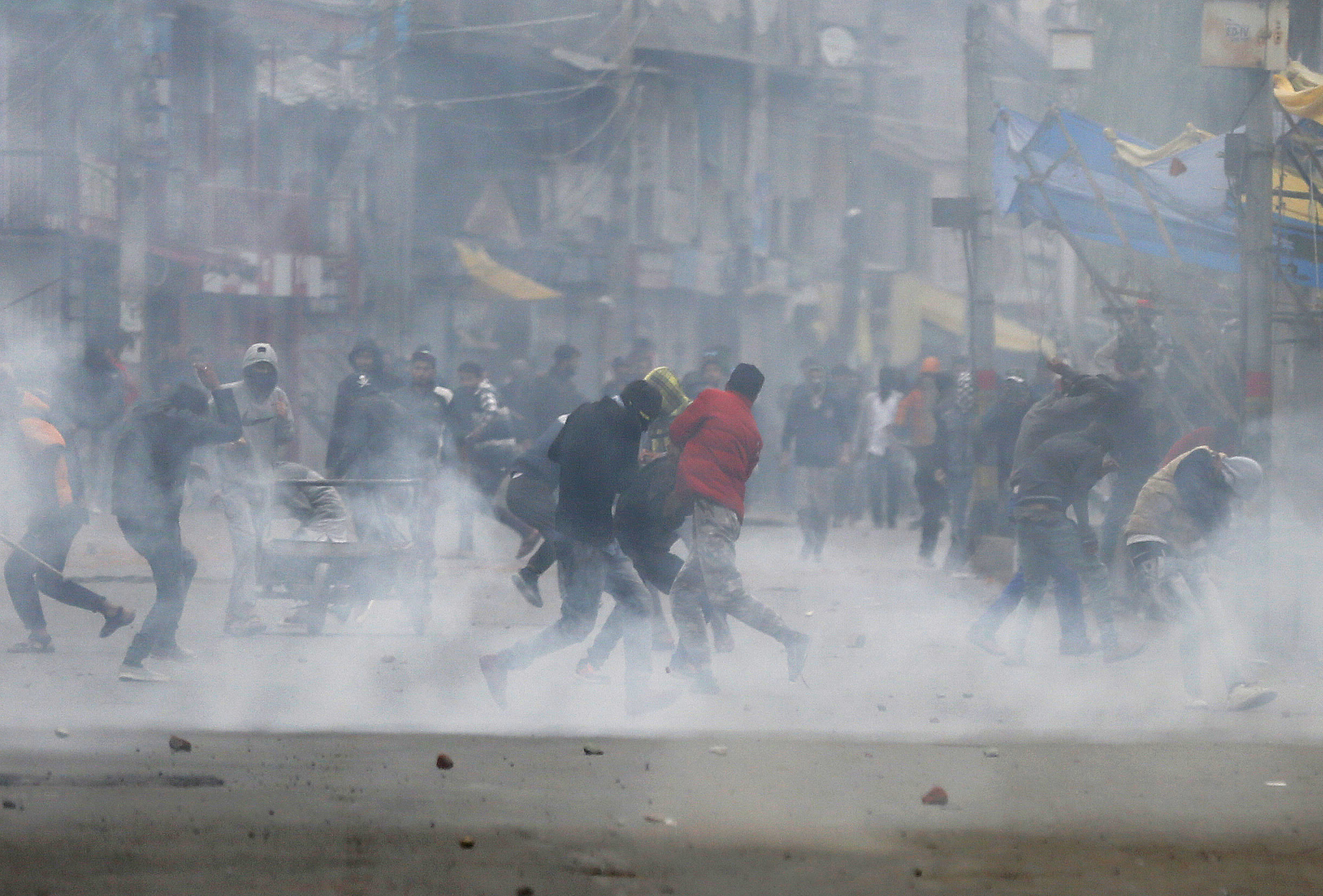 Kashmiri Muslim protesters take cover as Indian policemen fire tear gas and pellets as they clash during the fourth phase of local elections in Srinagar - AP