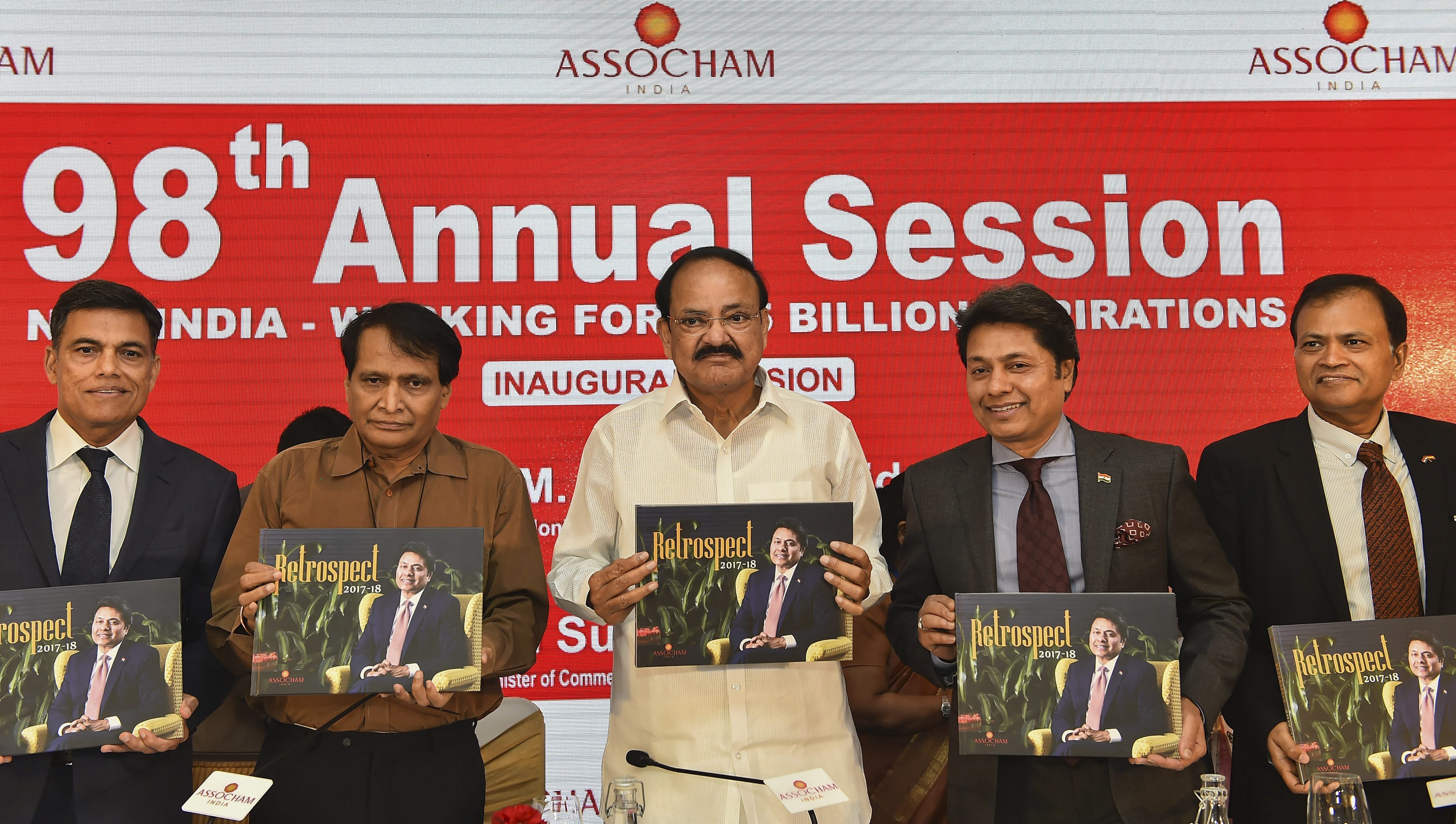 Vice President M Venkaiah Naidu (C) flanked by Commerce Minister Suresh Prabhu (L) and ASSOCHAM President Sandeep Jajodia release the orgainsation's 'Retrospect 2017-18' during the 98th Annual Session