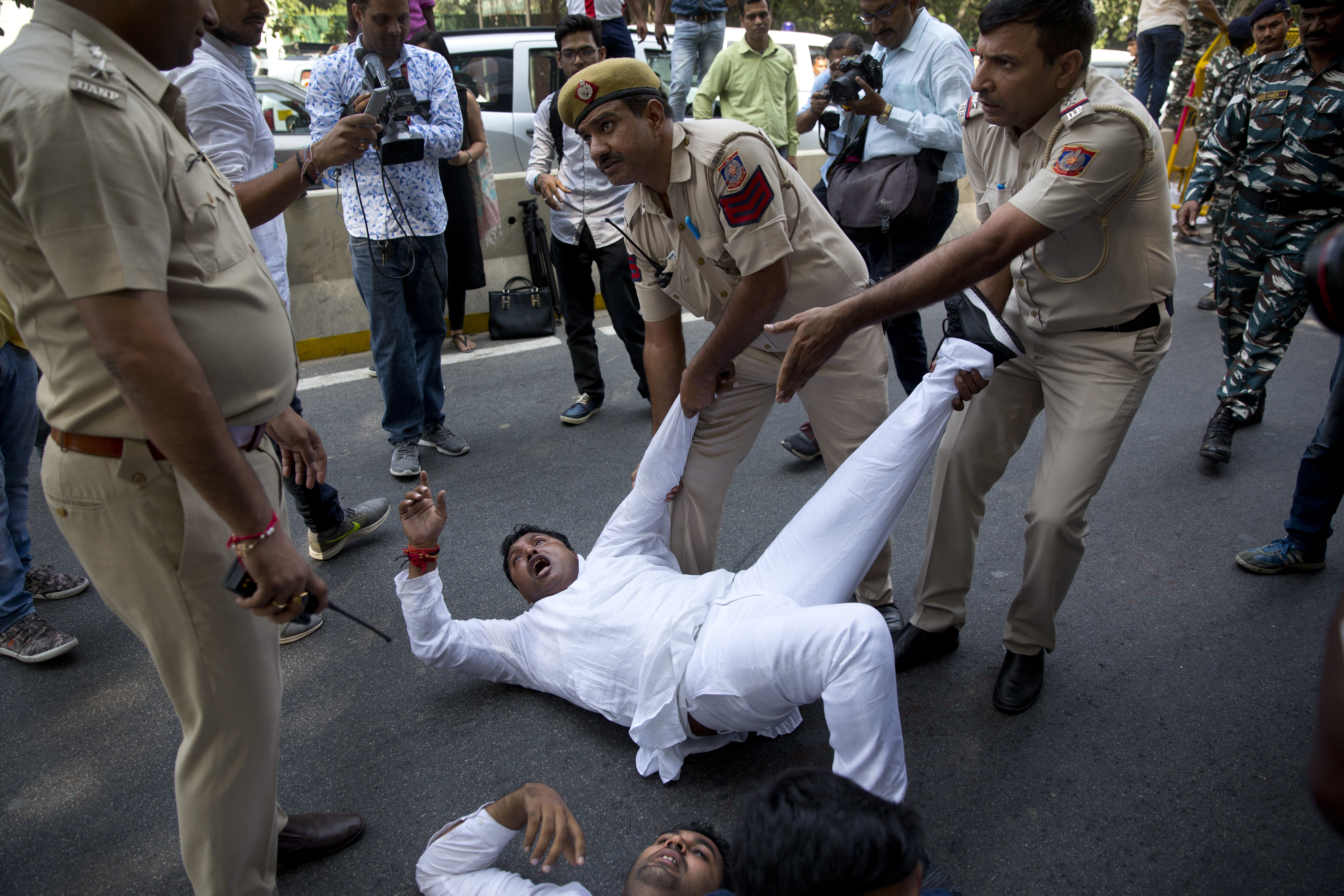 Indian policemen detain a Congress party worker during a protest against India's junior external affairs minister M.J.Akbar in New Delhi - AP