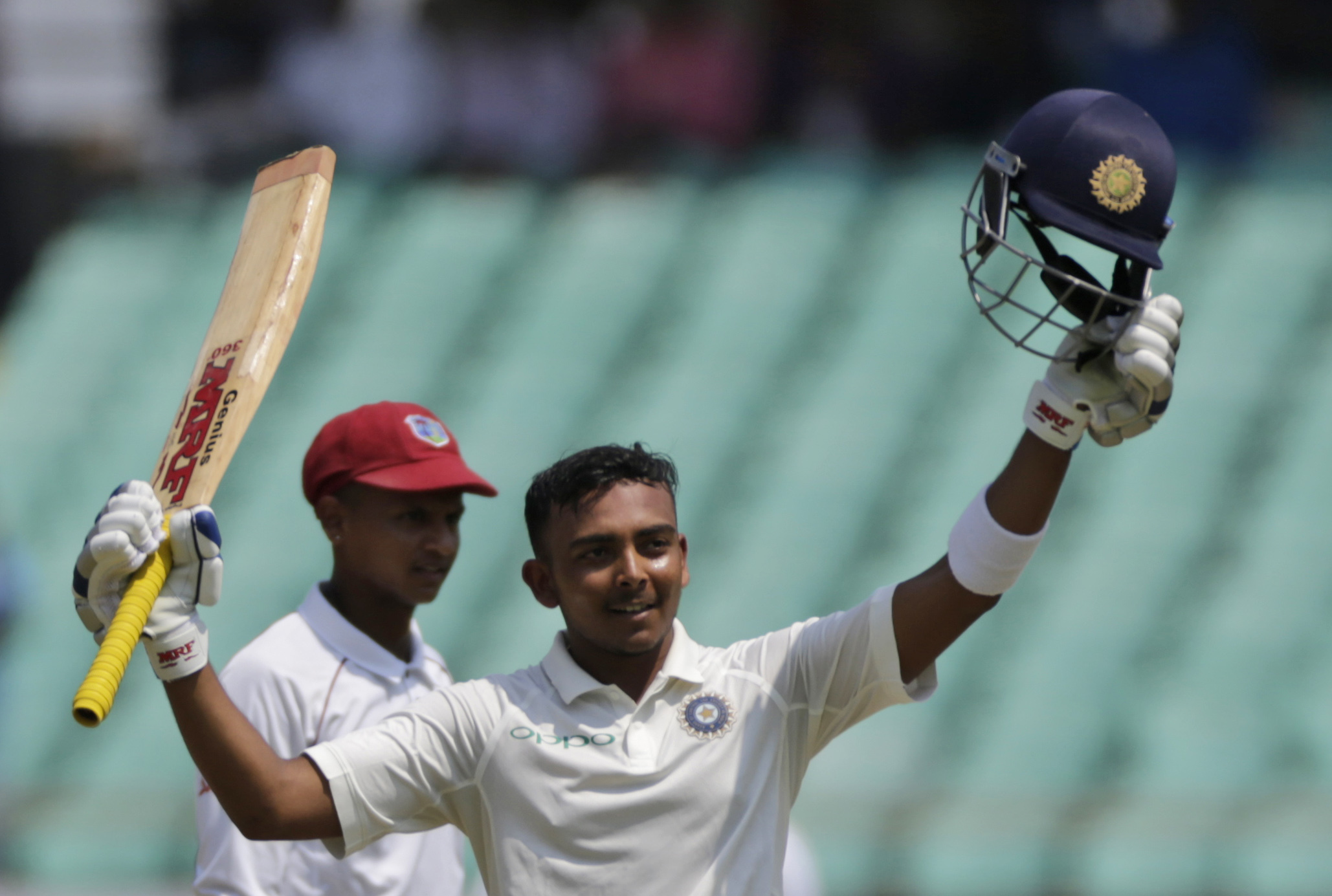 Indian cricketer Prithvi Shaw celebrates his century during the first day of the first cricket test match between India and West Indies in Rajkot - AP