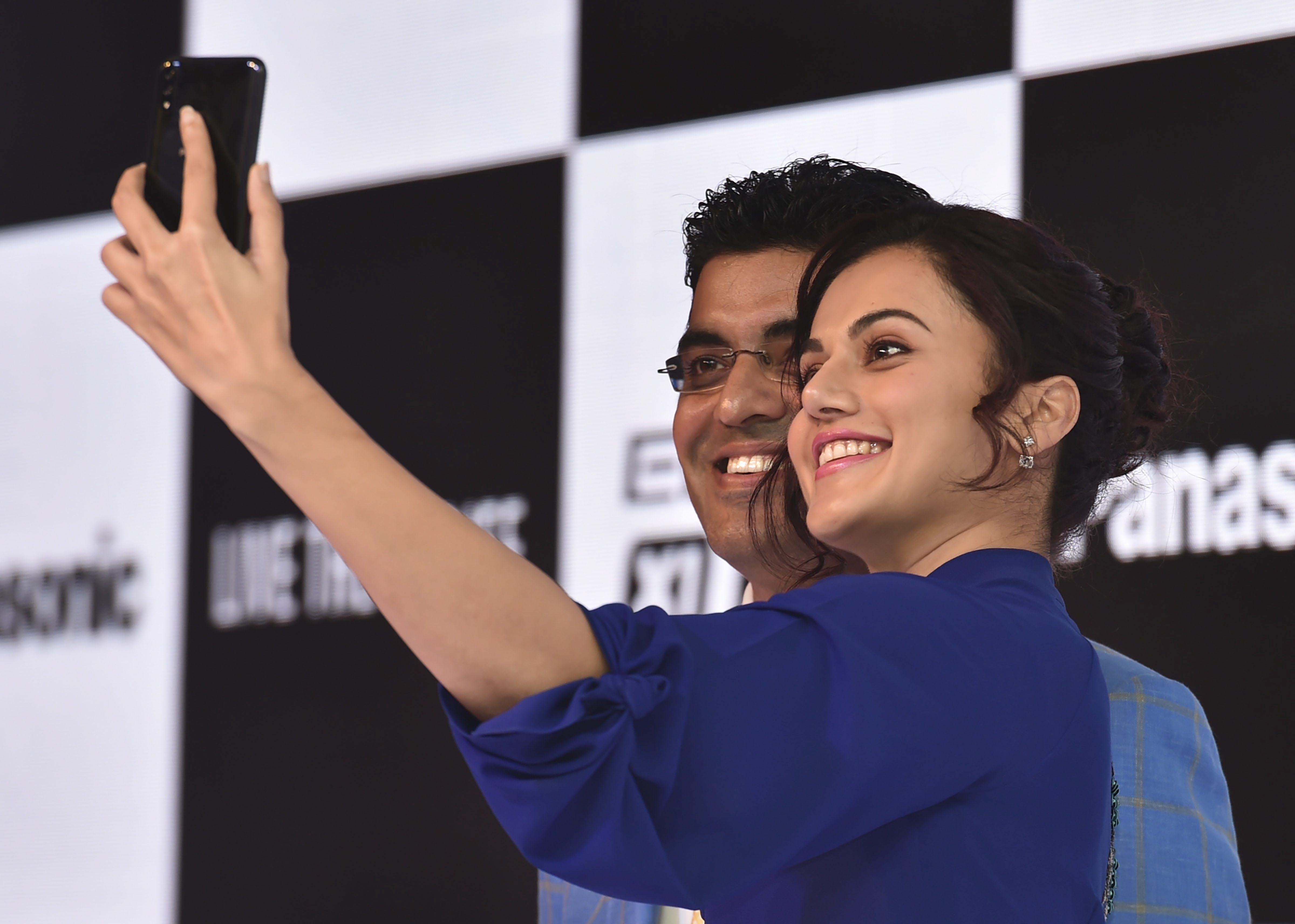 Brand Ambassador and Bollywood actor Taapsee Pannu takes a selfie with Panasonic India Mobility Division Business Head Pankaj Rana during the launch of Panasonic's smartphones Eluga X1 and X1 pro at a press conference, in New Delhi - PTI