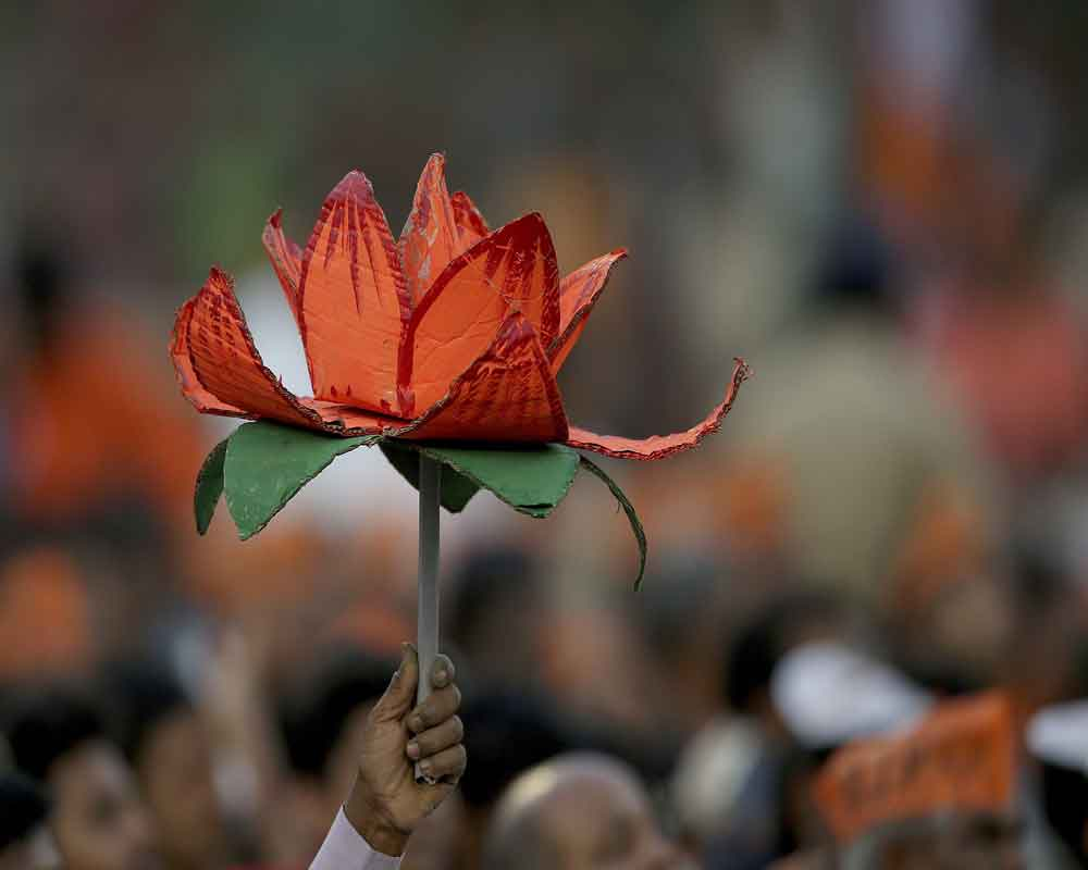 India's ruling Bharatiya Janata Party (BJP) supporter holds party symbol during an election campaign rally in Hyderabad - AP