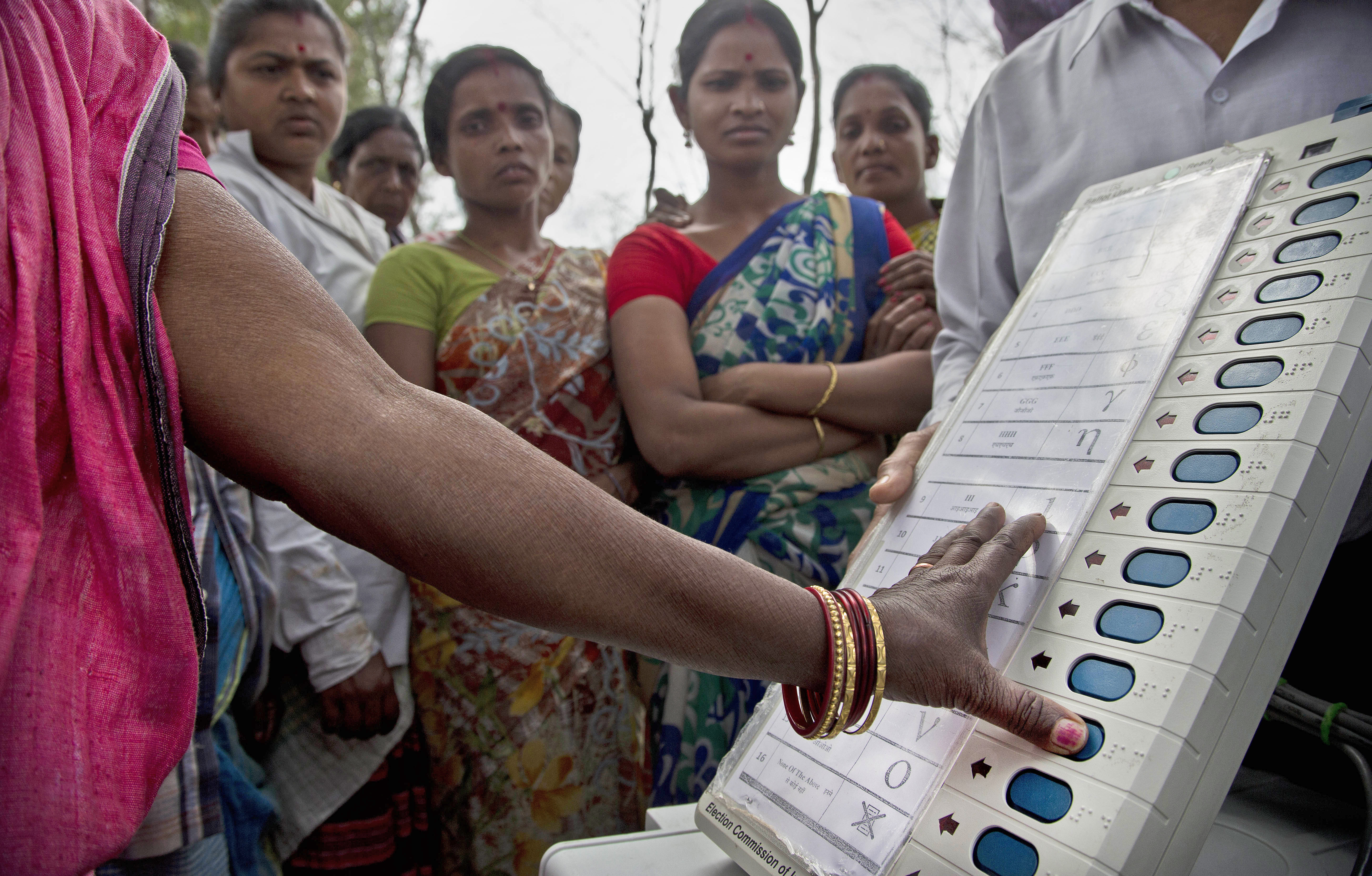 A woman casts her vote on the demo electronic voting machines and Voter Verifiable Paper Audit Trail or VVPAT during an election awareness drive by district administration amongst the tea garden laborers ahead of India's general election in Jorhat - PTI