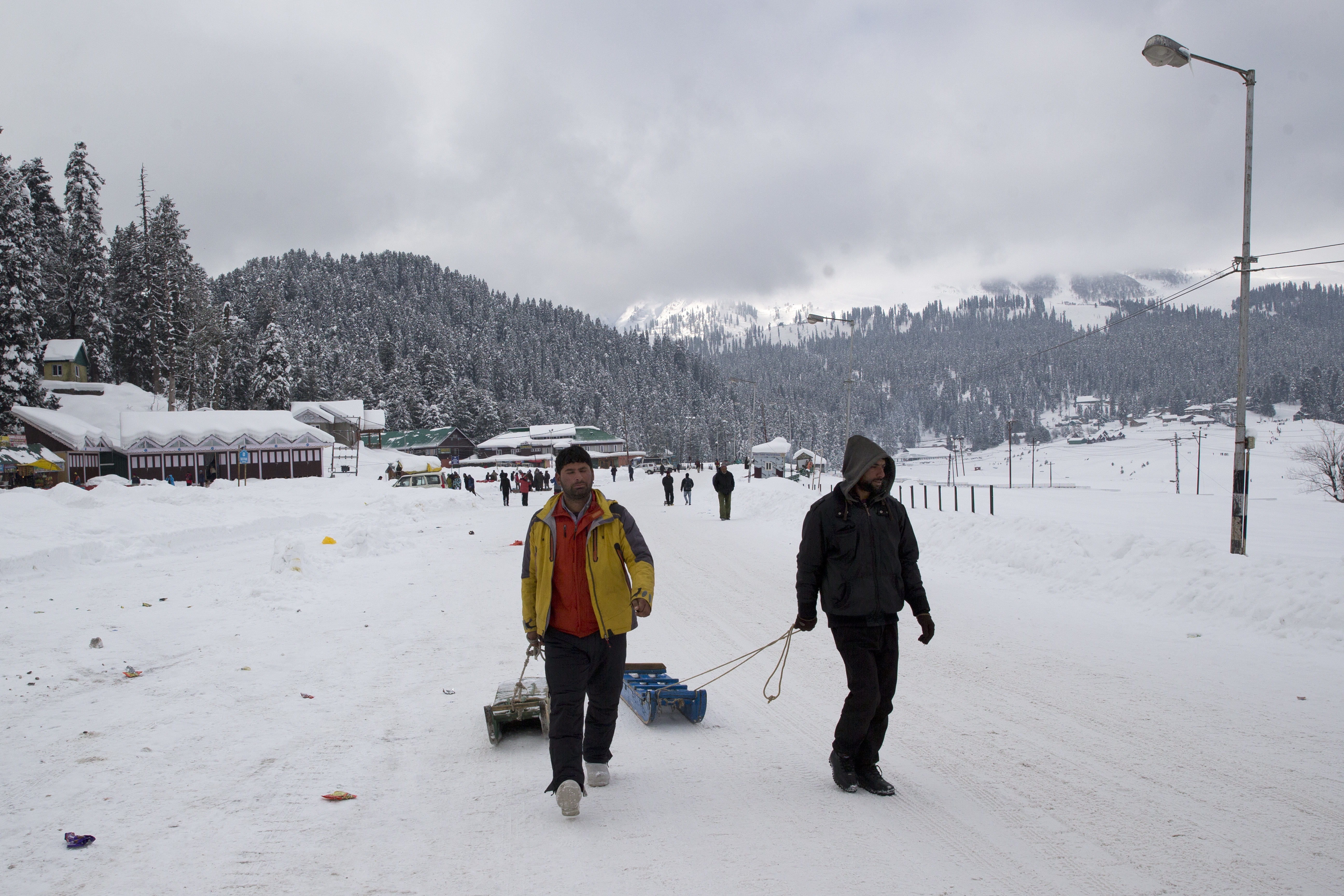 Kashmiri sledge pullers walk on a snow covered road in Gulmarg, 55 kilometers (34 miles) north of Srinagar, Indian controlled Kashmir - AP