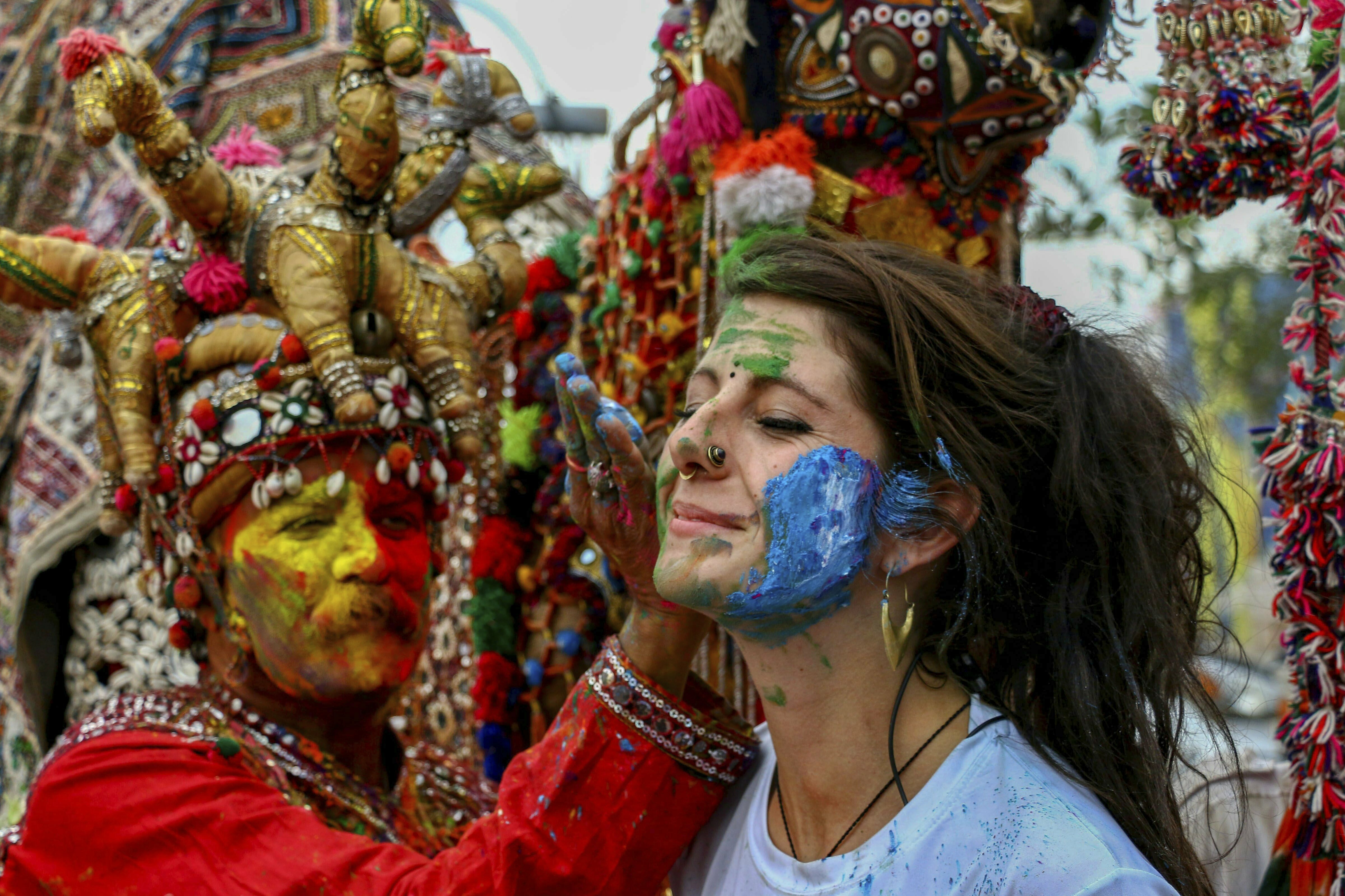 An artist applies colours on a foreign tourist during Holi festival celebrations, in Pushkar - PTI