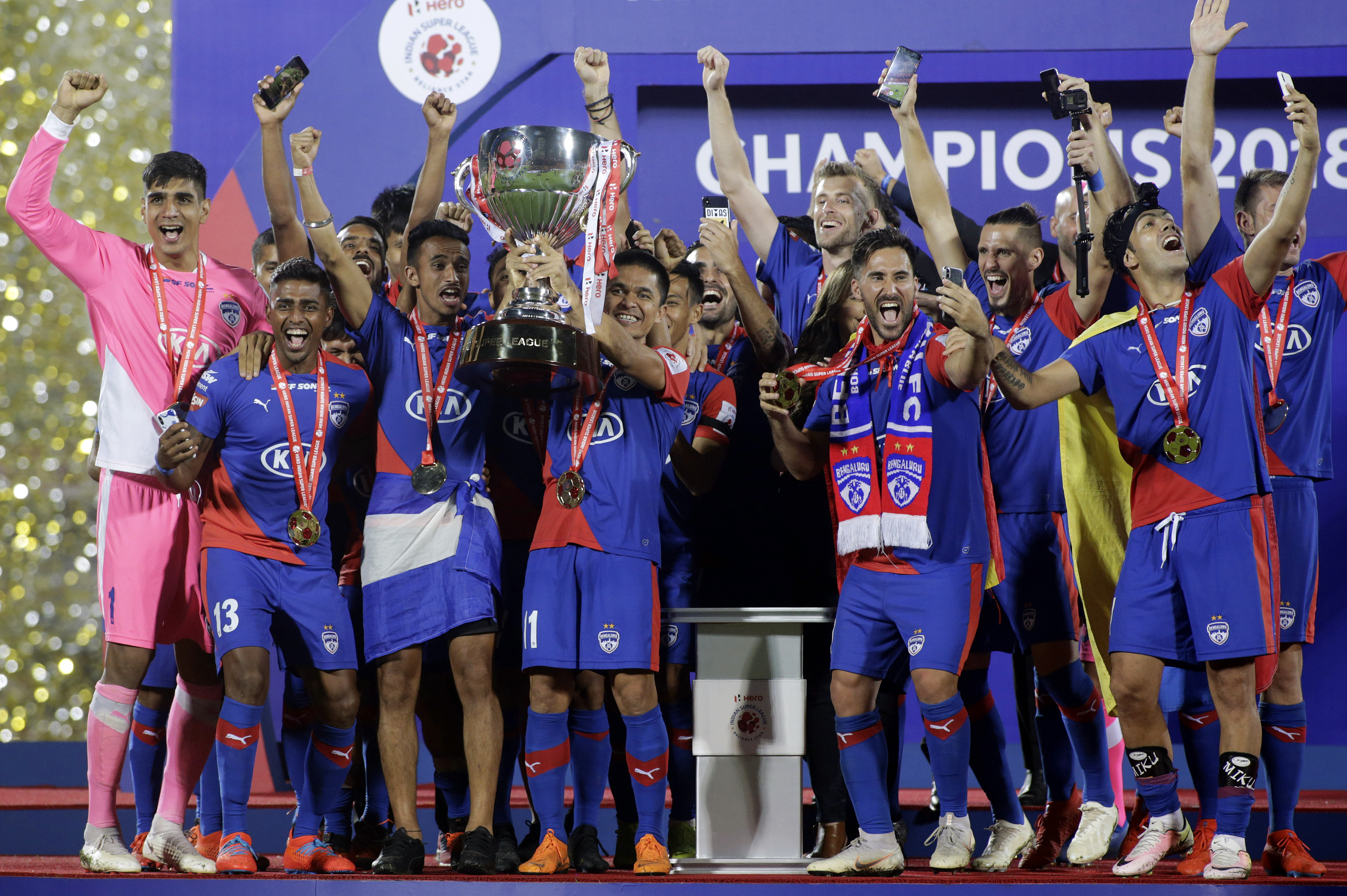 Bangaluru's captain Sunil Chhetri celebrates with teammates as he holds the trophy after winning the final of Indian Super League in Mumbai - PTI