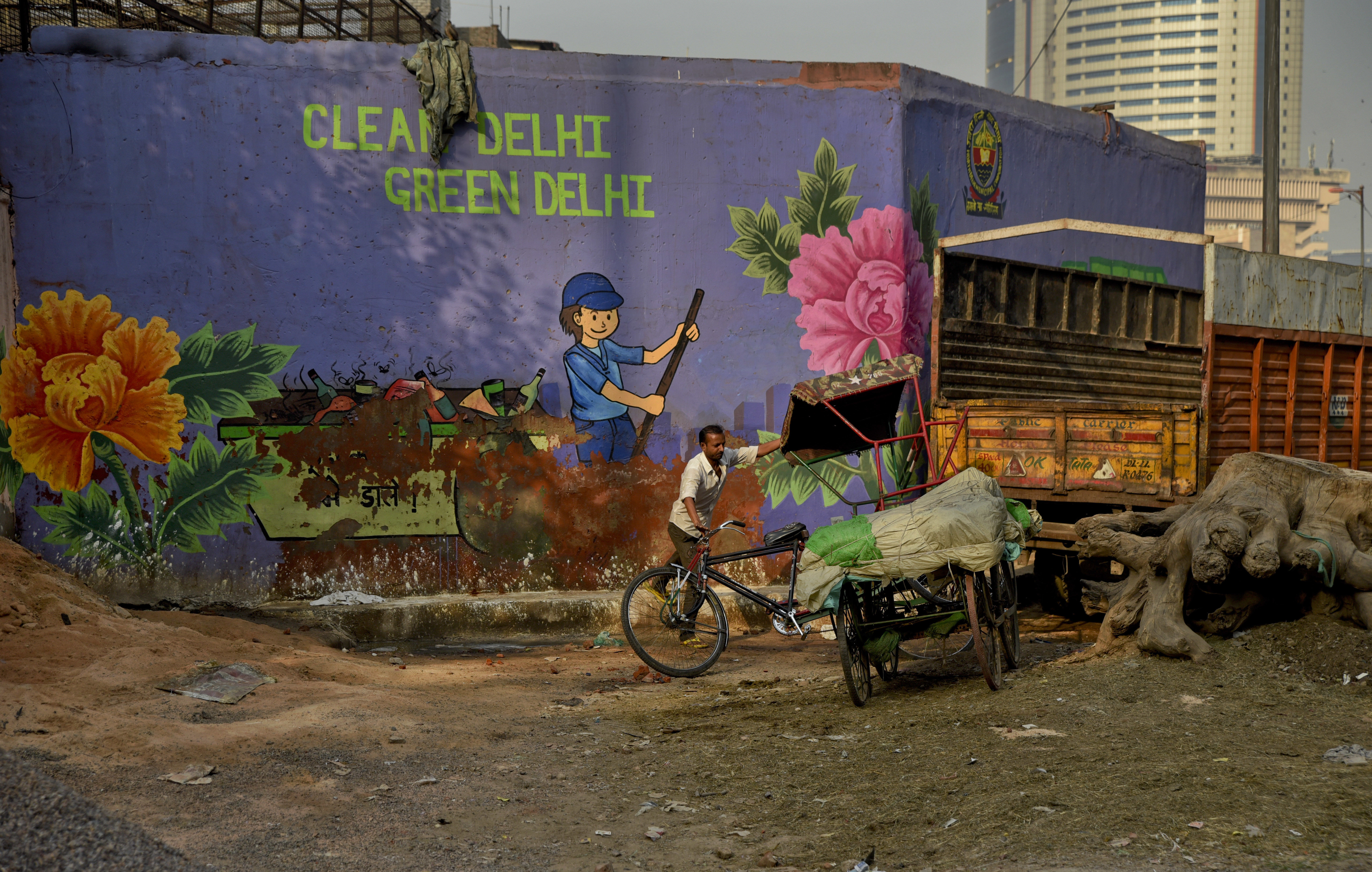 An Indian cycle rickshaw puller maneuvers his rickshaw past an awareness mural campaigning for a clean and green Delhi in New Delhi, India - AP