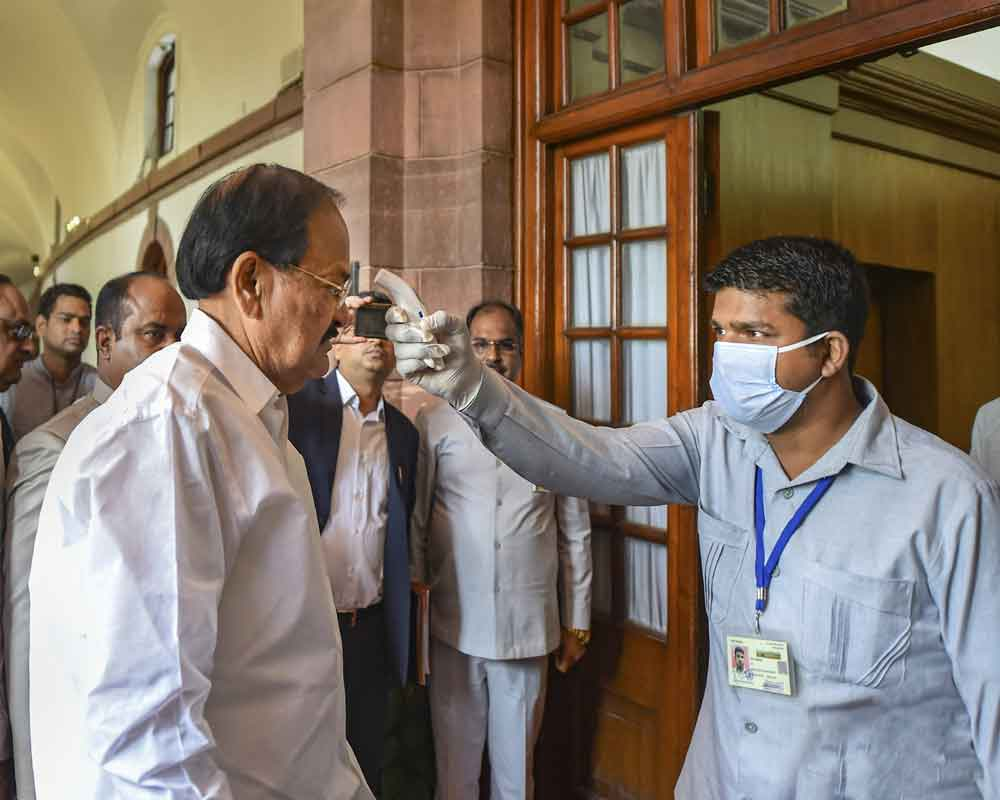 An official uses thermal screening device on Vice President M Venkaiah Naidu, in the wake of deadly coronavirus, as he arrives at Parliament House in New Delhi - PTI
