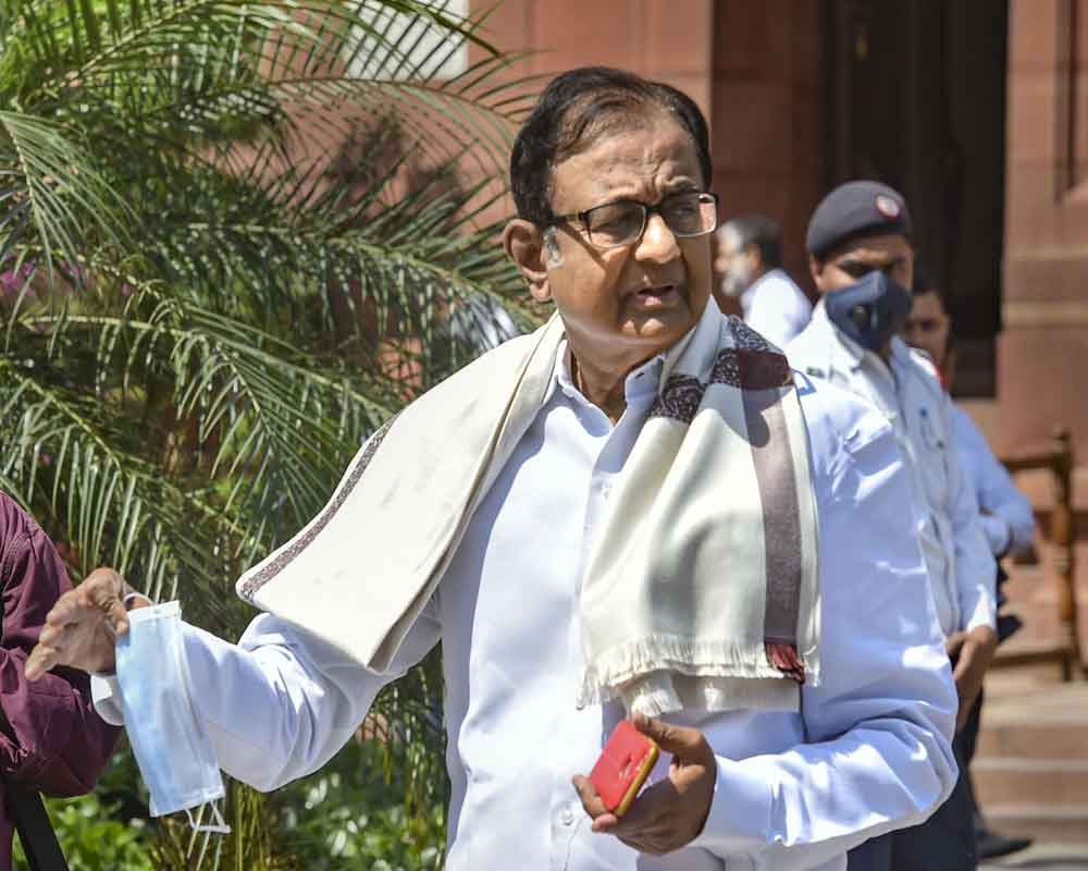 Senior Congress leader P Chidambaram walks holding a mask in his hand at Parliament, during the ongoing Budget Session, in New Delhi - PTI
