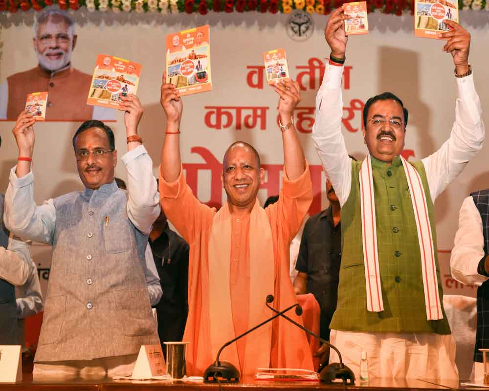 Uttar Pradesh Chief Minister Yogi Adityanath releases a publication during a press conference on completion of his three years in office at Lok Bhawan, in Lucknow - PTI
