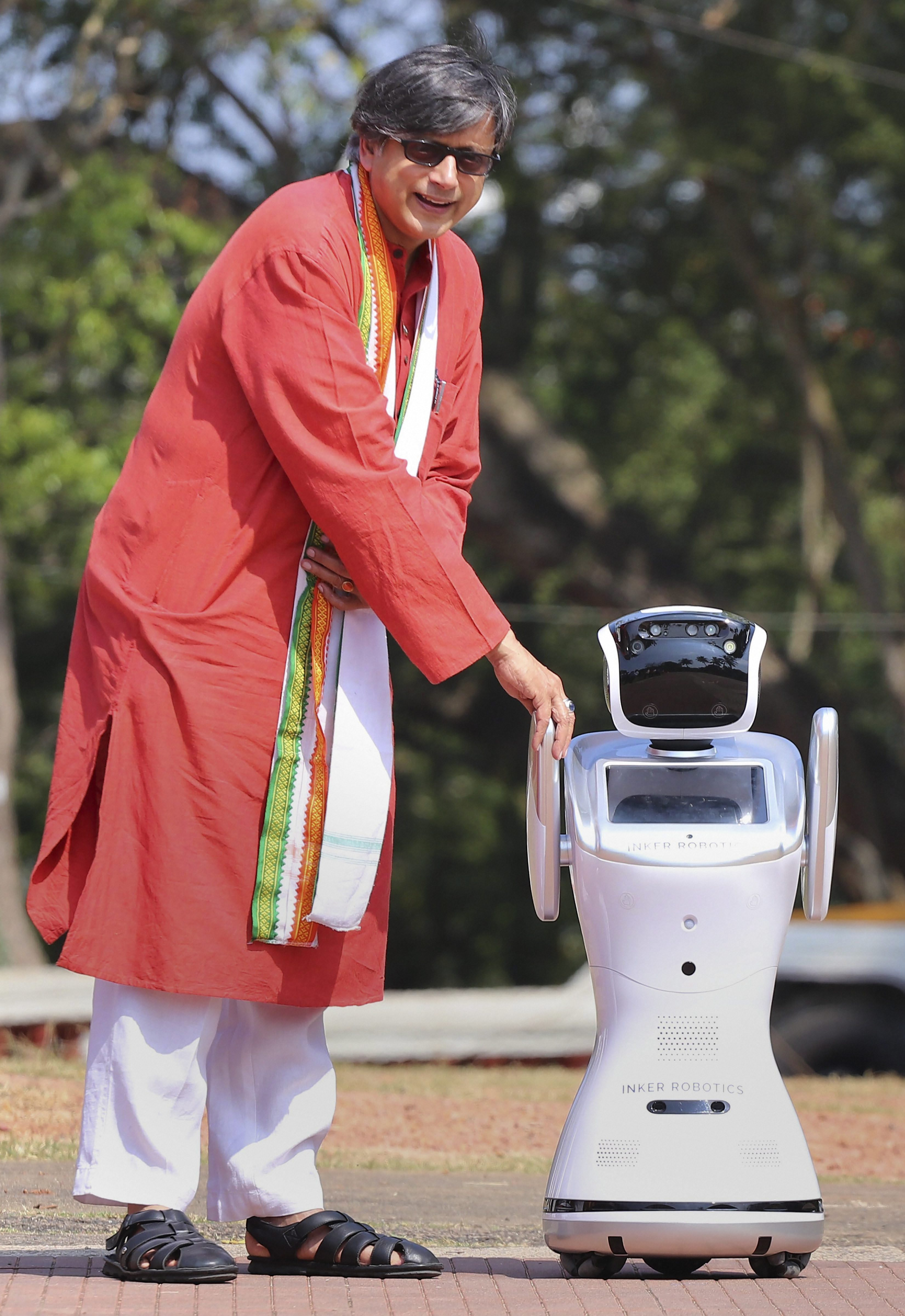 Senior Congress leader Shashi Tharoor with humanoid robot 'Inker Sanbot' at a function organised by International Foundation for Futuristic Education and Research and All-India Professional Congress, in Thiruvananthapuram - PTI